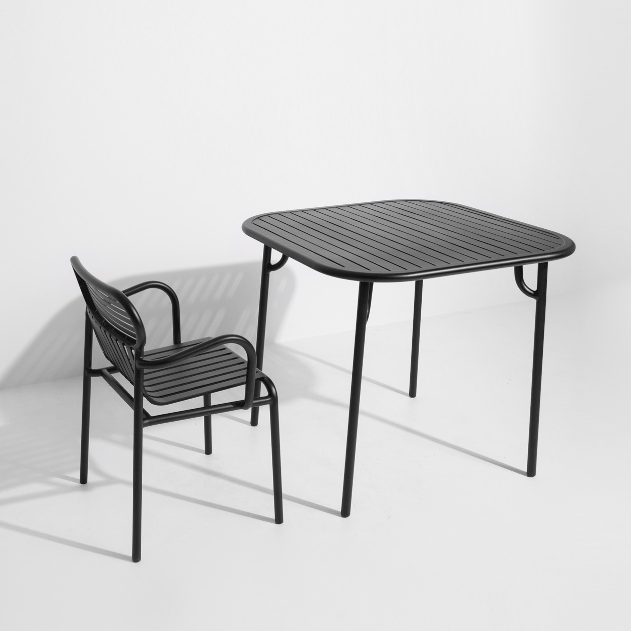 Week-End Square Table - The WEEK-END collection is a full range of outdoor furniture. Designed with practicality in mind, all of the seats are stackable. The Week-End collection is a complete range of outdoor furniture. The oval and circular shape drawn by the backrests makes them a graphic statement. The impact of the horizontal and vertical slats, so similar to stripes, highlights the full and empty spaces, asserting the identity of the collection.  | Matter of Stuff
