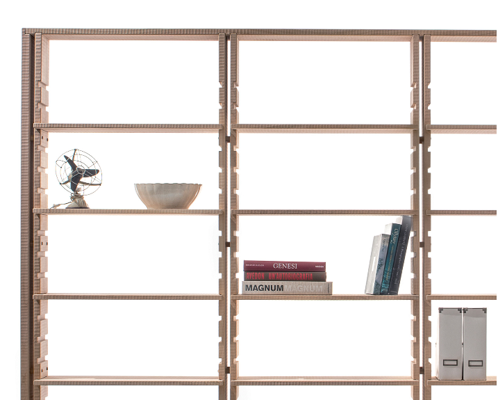 "Chiaravalle Bookcase - <p>Chiaravalle is a three-section bookcase made in solid wood. The shelves are easily adjusted for height, thanks to slots in the uprights. The structure is stabilised by stays in burnished steel at the back. It is manually finished on all sides using a plane. The entire manufacturing and finishing process is carried out manually in our workshop. The wood used for this item is linden, typical of the European climate zone and used in traditional Latin sculpture. With a faint grain, linden is distinguished by a soft but extremely ""bonded"" fibre: it, therefore, combines a certain lightness with great mechanical toughness. Its pale colour is highly valued and over time takes on a delicate pink hue. This structure is distinguished by its great rationality: the uprights define the image of the bookcase, while the metal stays accentuate its lightness. Functional and structural necessity become a motive for formal beauty.</p>