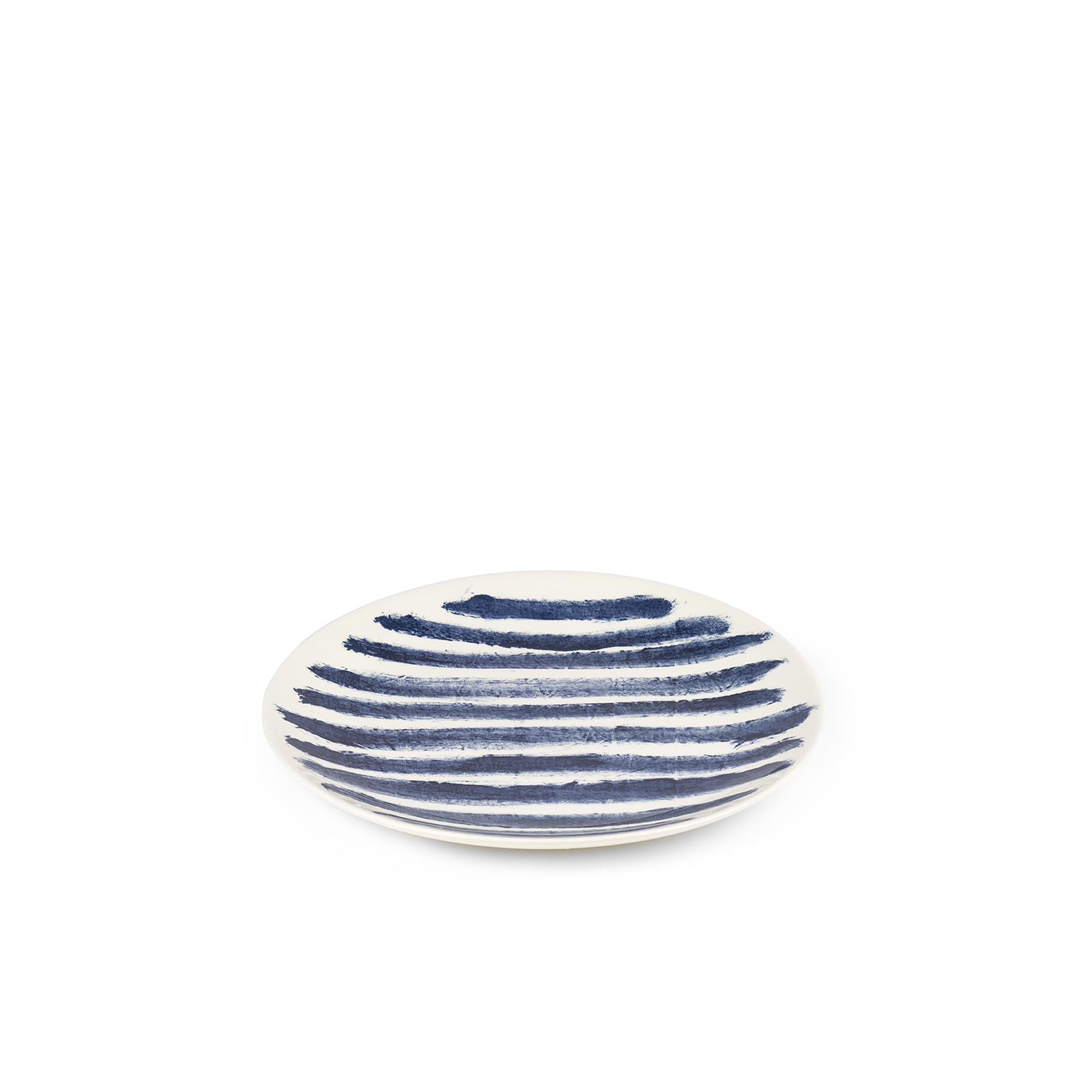 Indigo Rain Dinner Plate - Faye Toogood's addition to her range of ceramic designs for 1882 Ltd. puts a fresh spin on the forms and traditions of English creamware. Indigo Rain reinterprets the homely familiarity of blue-and-white striped crockery in a new design informed by the spirit of serendipitous discovery. Representing a streamlined take on our ceramic heritage, the fine earthenware employs the familiar tones of English Delftware: cream offset with a rich, deep blue. Broad bands of indigo glaze, like painterly washes of watercolour, are applied to rough canvas and then transferred to the pieces – the characteristic grain of the fabric imbues the delicate ceramics with the hardworking spirit of dark-dyed denim.  | Matter of Stuff
