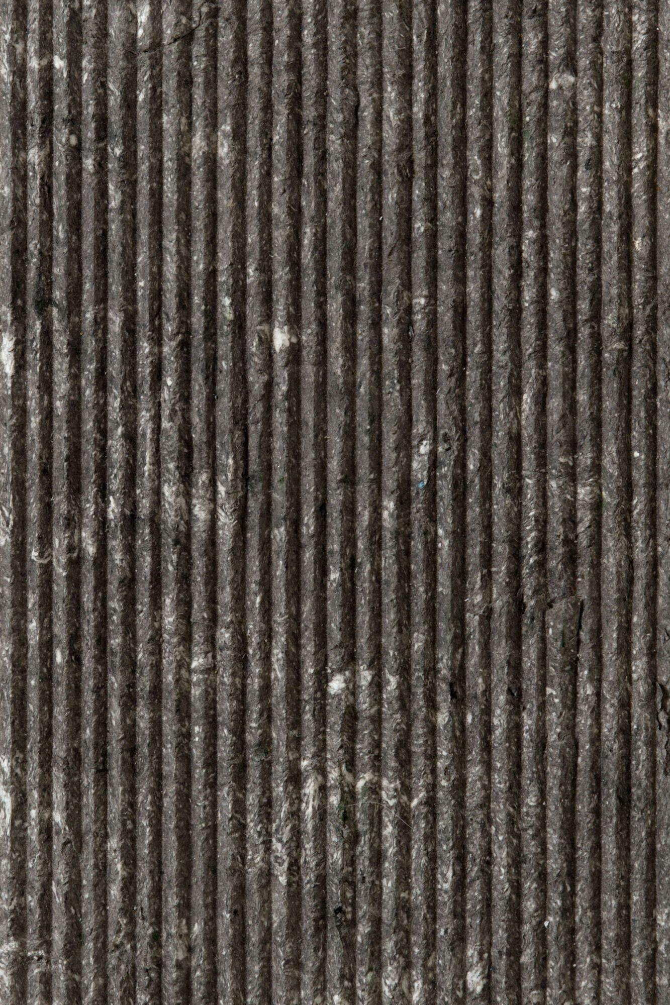 """Grey Veins Ruts - Obtained by stretching the impasto first by hand and then with CNC machining, Ruts alternates between flat portions, reminiscent of stone, to rectangular sections to create a succession with a solid and fortunate rhythm. The """"cadence"""" of its grooves can be more or less dense, continuous or interrupted, but in each of its versions and in all the different colors, Ruts reveals, thanks to the intervention of the machine, the material uniqueness of paper pulp. They are indeed hard, mechanized cuts that speak of the very fiber of the paper as it pushes toward new dynamic and formal borders. 