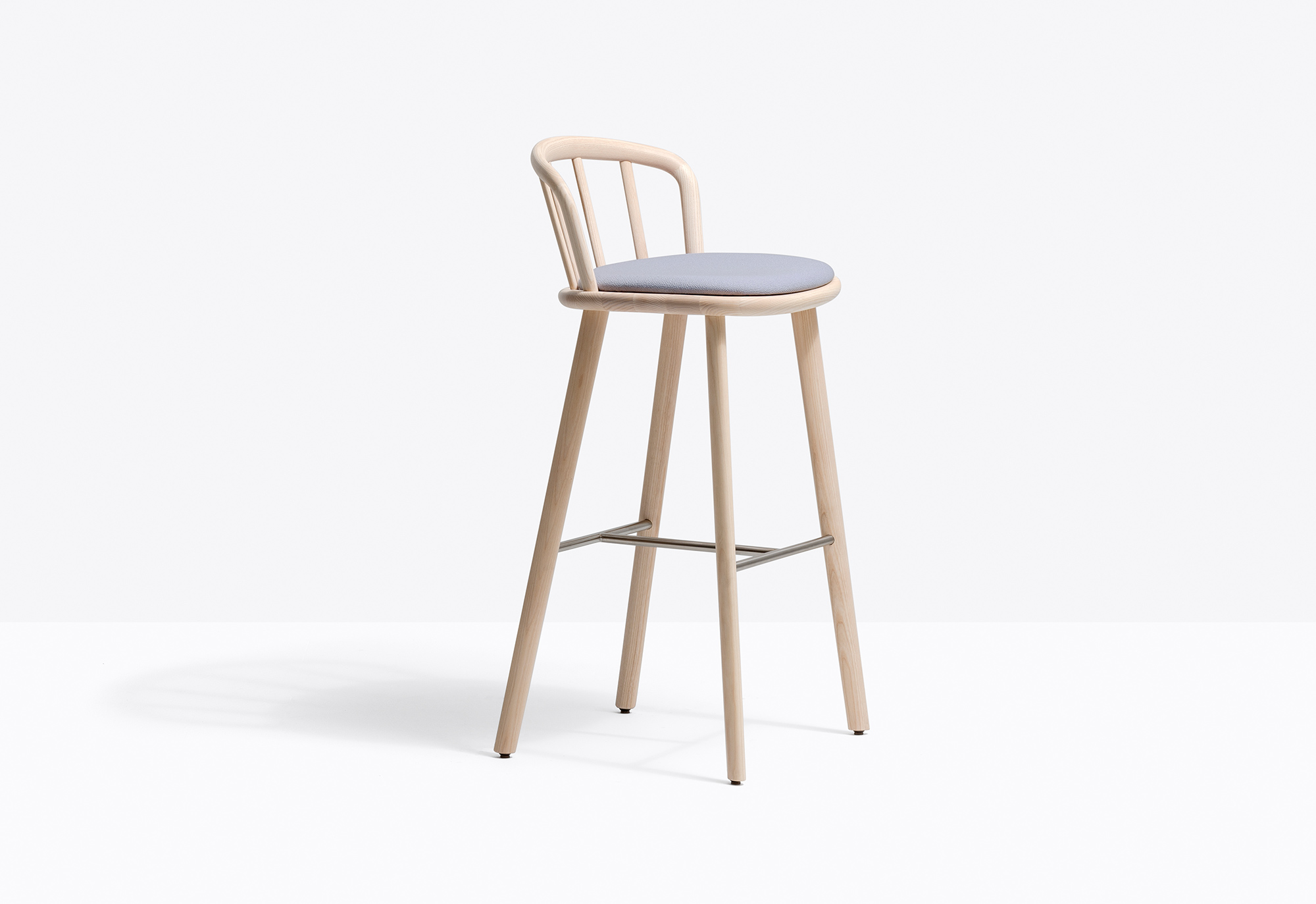 Nym Stool with Cushion - Nym barstool adopts the archetypal structure of the English Windsor chair, reinterpreting and streamlining it to reflect industrial manufacturing systems. The arched backrest in elliptical-section bentwood flows seamlessly into the shaped solid wooden padded seat to form an armrest. Solid ash wood legs and a stainless steel footrest. Seat height 775 mm. | Matter of Stuff