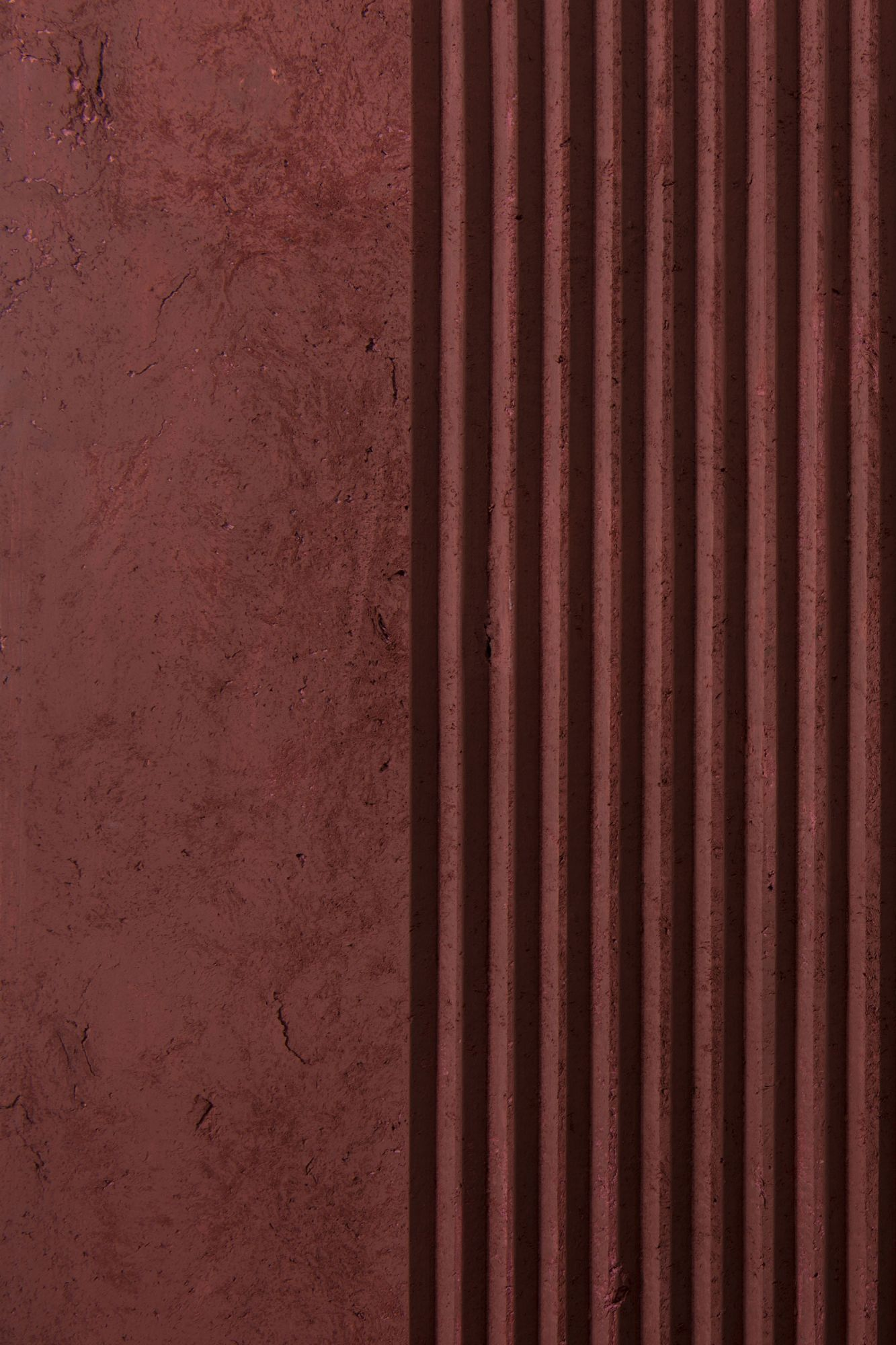 """Red Ruts - Obtained by stretching the impasto first by hand and then with CNC machining, Ruts alternates between flat portions, reminiscent of stone, to rectangular sections to create a succession with a solid and fortunate rhythm. The """"cadence"""" of its grooves can be more or less dense, continuous or interrupted, but in each of its versions and in all the different colors, Ruts reveals, thanks to the intervention of the machine, the material uniqueness of paper pulp. They are indeed hard, mechanized cuts that speak of the very fiber of the paper as it pushes toward new dynamic and formal borders. 