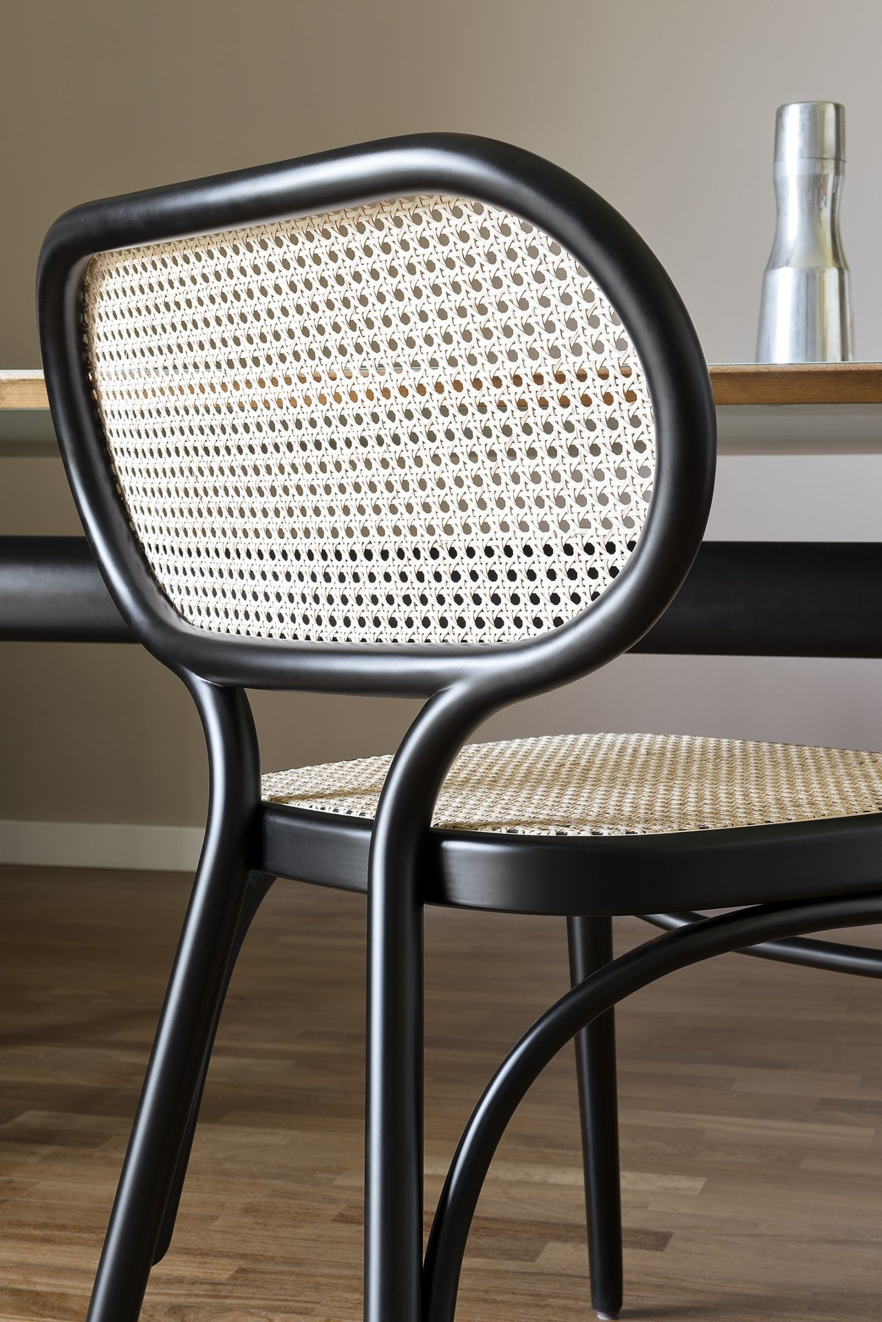 Bodystuhl Upholstered Chair with Woven Cane Backrest - This stunning chair boasts the virtuous touch of beechwood curved with steam. The result is a sinuous silhouette with a generous seat and an ergonomic backrest, both in exquisite Viennese straw. The colour of the textured straw strikingly contrasts with the black lacquer finish of the wood. Either by a modern table or combined with the Lehnstuh Lounge Chair for a cohesive look, this piece will add a sophisticated and timeless touch to contemporary home. | Matter of Stuff