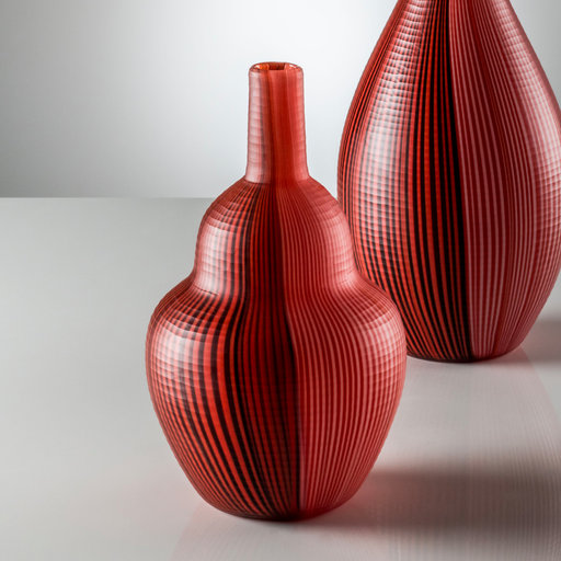 "Tessuti Battuti Vase - This superb vase designed in 1940 by Carlo Scarpa is part of a numbered edition. The mouth-blown glass is handmade incorporating different techniques to obtain a striking visual effect evoking the folds of pleated fabric. Two-tone brick red watermark stripes follow the sinuous profile of the vase with glass rods (""canne"") encased in an opaque overlay using the ""filigrana"" method and finished in ""battuto"" to confer a textured surface.