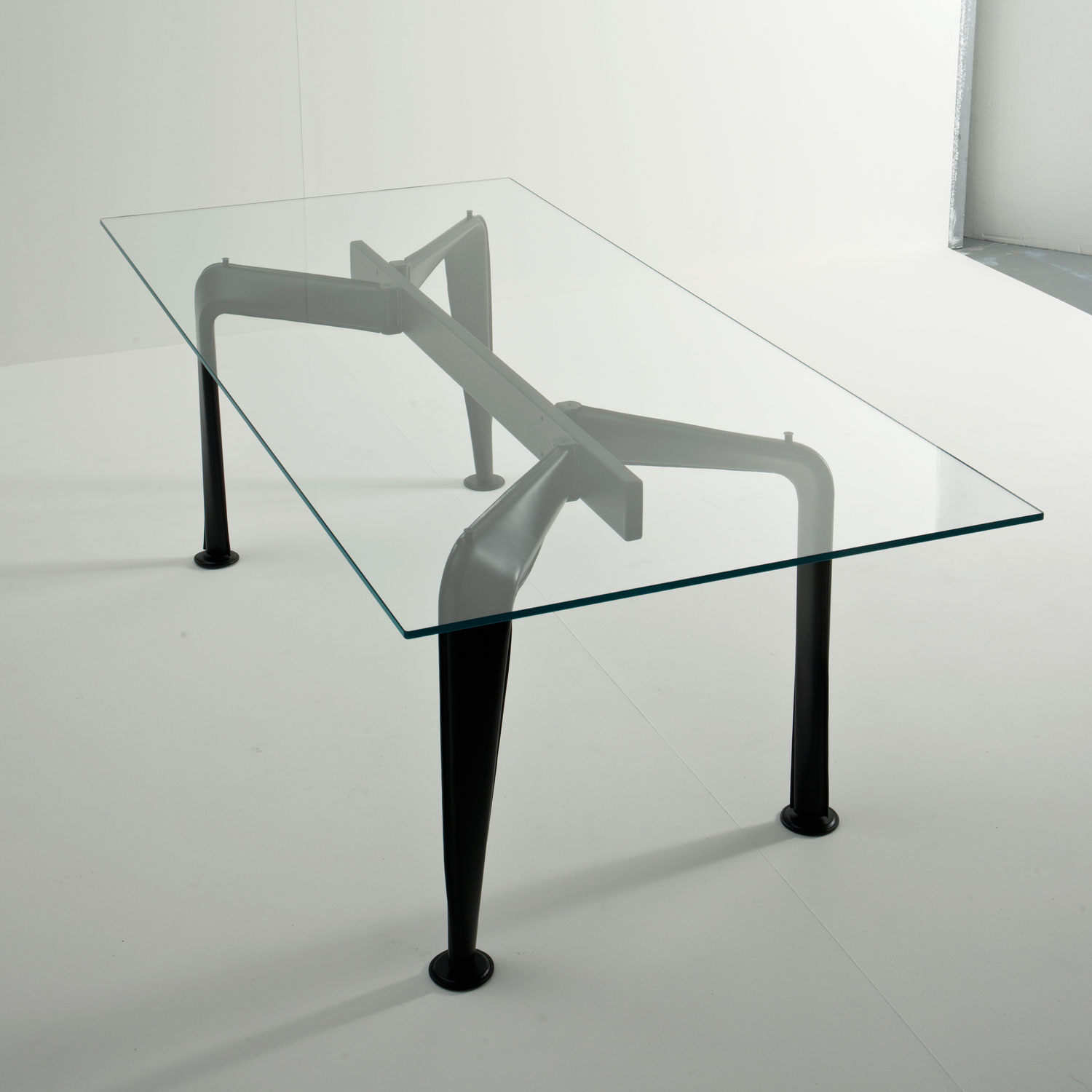 Asymmetrical Table Glass - This large and generous table evokes the striking shape of an insect, thanks to two sets of different legs that support a top in tempered glass with round corners. The legs are in steel upholstered in leather, available either in natural as in this case or in black and they can be combined together symmetrically or asymmetrically. The central support is in metal painted in black with epoxy dust that can be also covered in natural or black leather. Modern and sophisticated, this piece will make a statement in contemporary decor.