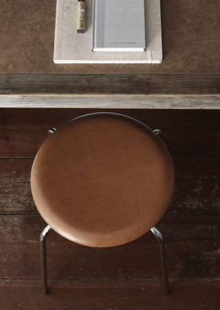 Dot Stool - <p>Arne Jacobsen designed the beautiful Dot stool in 1954 in the process of creating the Ant chair in collaboration with Fritz Hansen.</p> <p>The four-legged stool is available with a chromed steel base, the seat is clad in walnut coloured wild premium leather. Actually, it uses leather left over from the crafting of the Egg and the Swan.</p> <p> The Monochrome black version has a contemporary dusty matt appearance and the base in black powder coated steel compliments the silky and smooth seat in intense leather. </p>  | Matter of Stuff