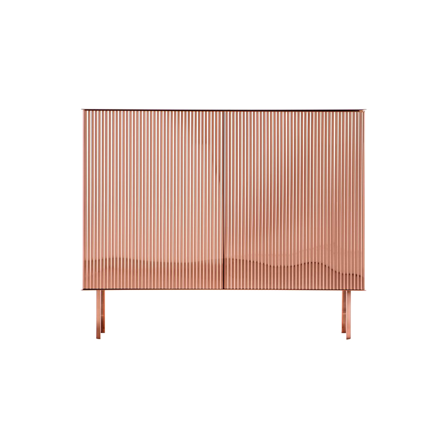 Elizabeth Sideboard - Like a ballerina on her toes, Elizabeth gracefully unfurls her luminous dress, as if made of pleated fabric. The characteristic folds add movement to the metal sheet along the surface of the cabinet, transforming each reflection into light. In an interplay of airiness and tension, elasticity and rigour, the metal vibrates with the rhythm of its pleats. Available in steel, brass or copper, Elizabeth gives shape to a new way of imagining unambiguously feminine metal furniture.  Cabinetclad in pleated metalon all sides. Push-open doors.Limited edition.  Inner Structure Mat lacquered RAL 7013 wood   Matter of Stuff