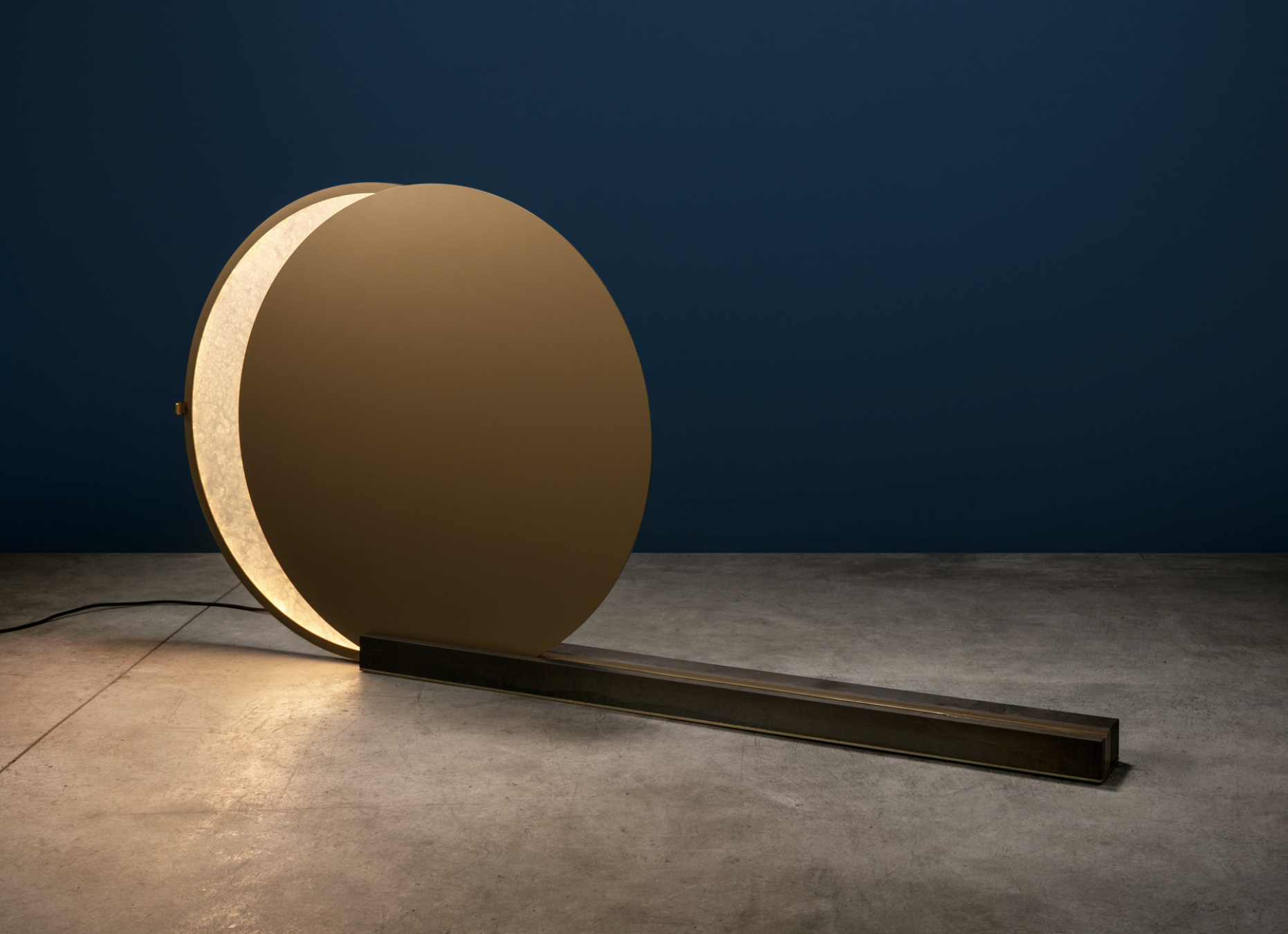 Alchemie F Floor Lamp - The antithesis between light and dark, between Sun and Moon, is everlasting, like part of the same flow of existence. Many allegorical meanings have been given to the necessary relationship between two elements that each exist as a consequence of the other. The new lamp Alchemie, designed by Giulia Archimede for Catellani & Smith, investigates this dimension whose components are diametrically opposed but always, and for ever, connected. Alchemie is an exquisite sculpture composed of two discs: the former, made of alabaster and lit by LEDs, stays fixed, while the latter slides on a track-base made of Medea limestone. The interaction between light and shade reaches its peak the moment when the two discs overlap and almost mimic an eclipse.   Matter of Stuff
