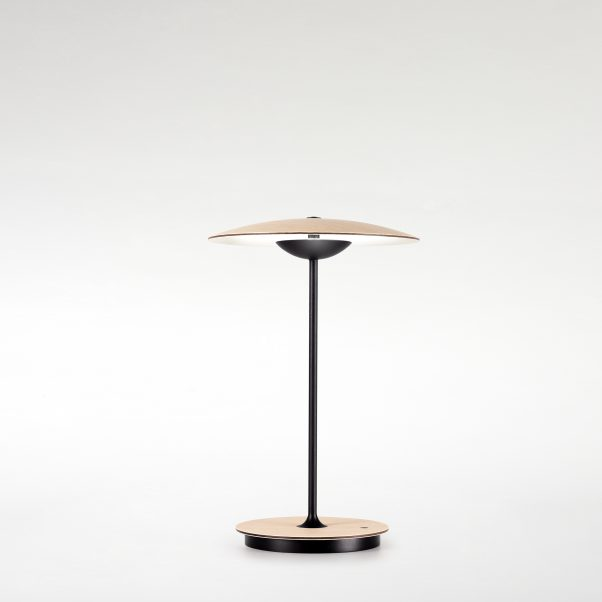 Ginger M Table Lamp - Wood is a great ally of cozy lighting. It is a material that is hard to mold, a challenge that the Ginger collection neatly resolves. The combination of sheets of wood, paper and resins pressed together under high pressure achieves a laminate that appears almost entirely flat, which discreetly lights up spaces with indirect light.  The Ginger collection has been expanded over time to provide solutions to different lighting needs, and is available in pendant, table, wall, and floor lamp versions. This time, we are adding a new, smaller suspension lamp, a portable table lamp, another version of wall lamp with a movable arm, and three different sizes of flush-mount wall lamps. The latter boast extraordinary structural simplicity, and can be combined with each other to great effect.  Thanks to a rechargeable lithium-ion battery, the new portable table version of Ginger allows spaces to be lit independently with utter freedom, and with no need for wires. | Matter of Stuff