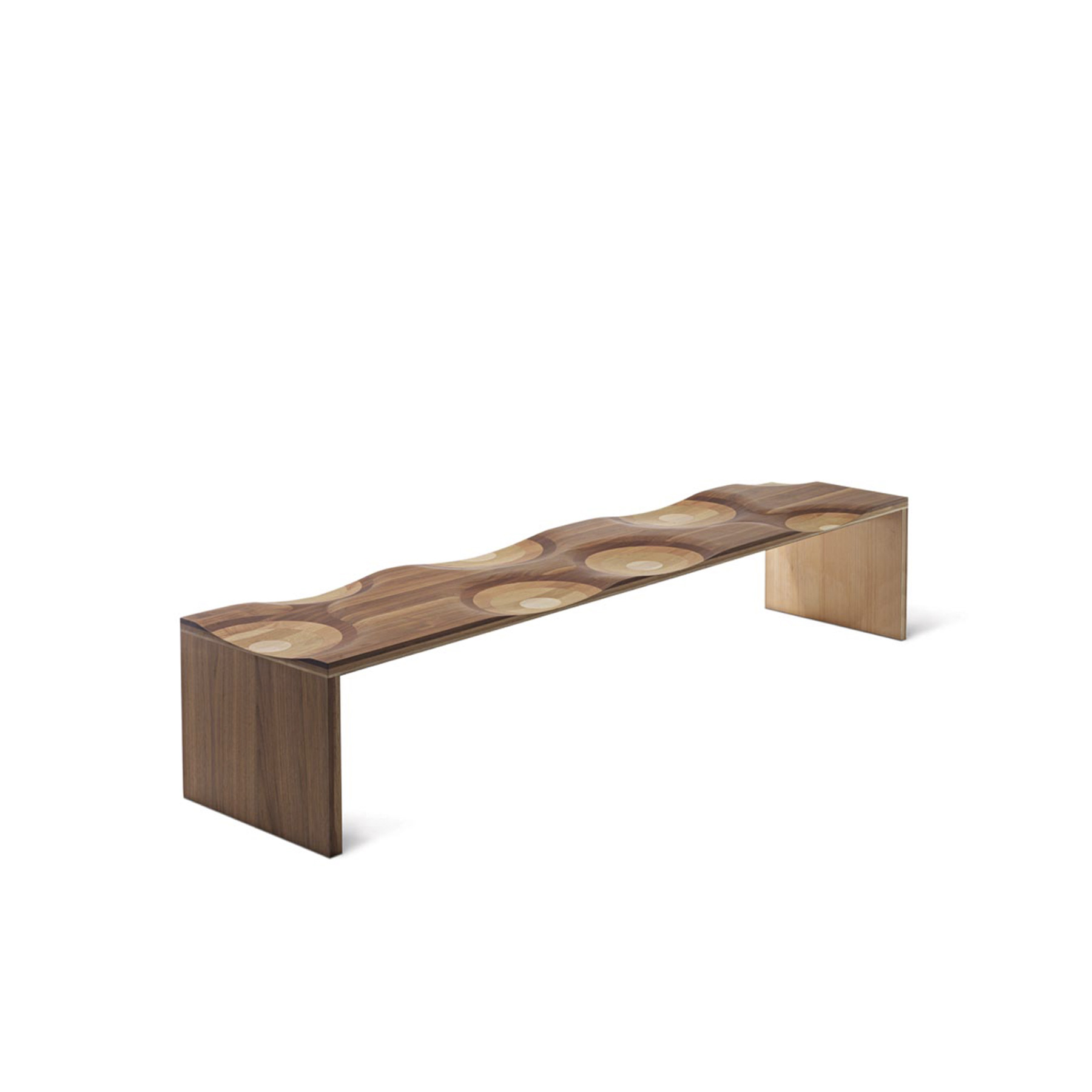 Ripples Bench - Ripples, winner of the 2004 Compasso d'Oro, is made of a laminated composite of five different solid woods. Slide your hand along the surface to enjoy the seamless transitions between walnut, mahogany, cherry, oak, and ash. The seat is reinforced with a hidden metal bar. This enveloping seat, carved with mastery, is hand-finished to produce an elegant polychromatic effect arising from the ductility of the wood. A true icon of international design, Ripples is a bench suitable for home users, commercial environments, and public spaces.