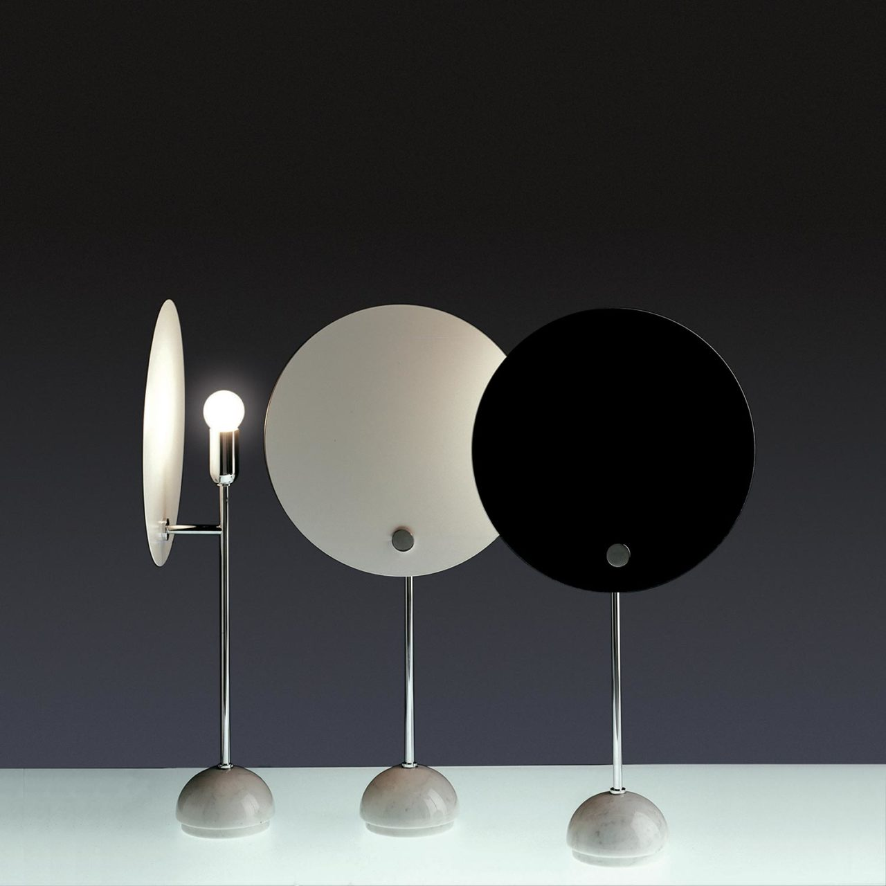 Kuta Table Lamp - <p>Kuta is an indirect light aluminium lamp with a circular reflector in aluminium, which shields the lighting distribution, giving the effect of a solar eclipse. The circular screen is painted in white and black, the stem and the metal small parts and hemispherical support are chromed. Table version with base in white marble. </p>