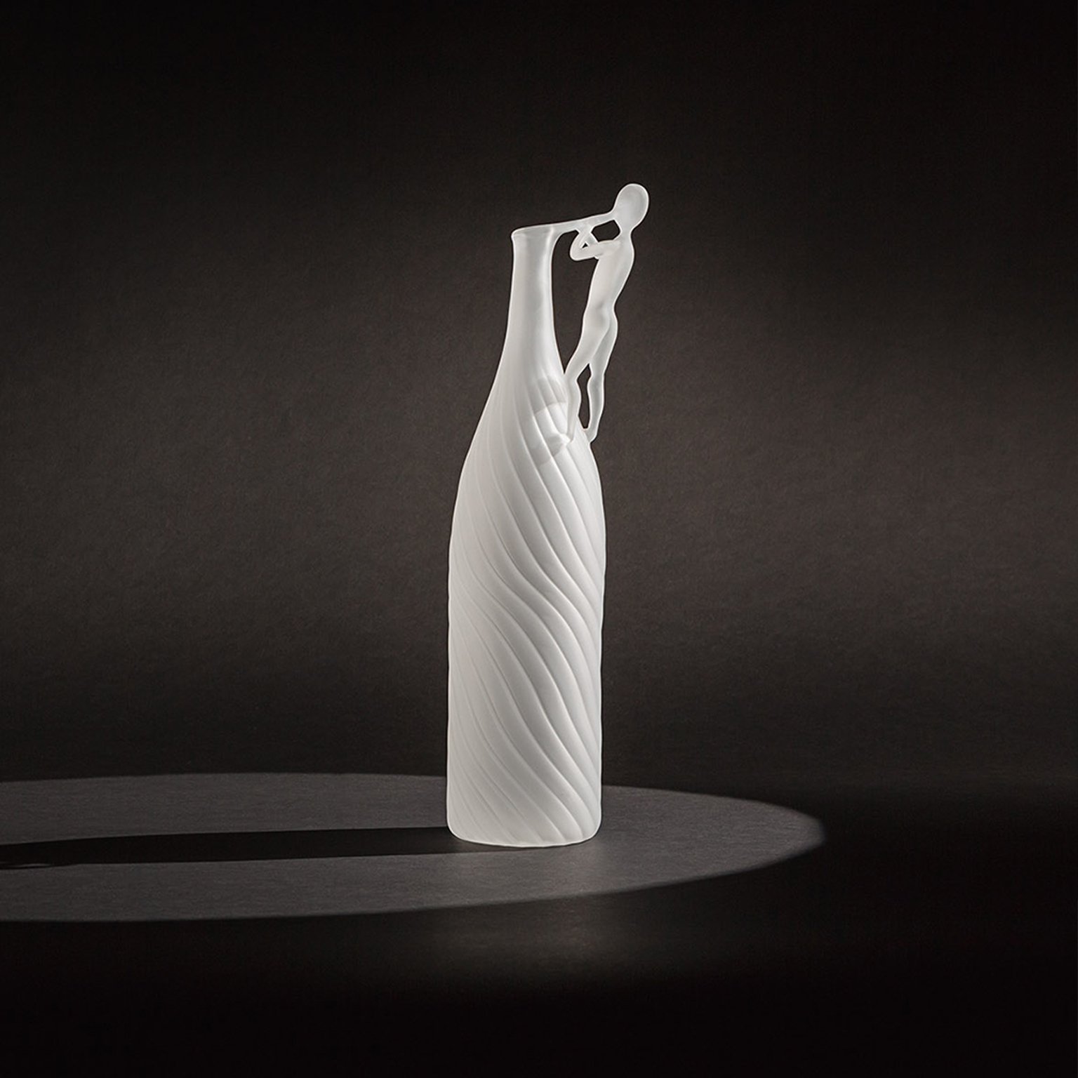 "The Blowing Man Bottle - The Blowing Man is a collection of 5 pieces in hand blown borosilicate glass in limited edition of 29 pieces, the story through the poetic and oneiric interpretation of the art of glass blowing.The collection becomes the theatre where ""man"" is once again the protagonist together with the object, and through the object itself, in a game of light and shadows that highlight the high-end handwork through the poetry of gestures delicate like breaths.