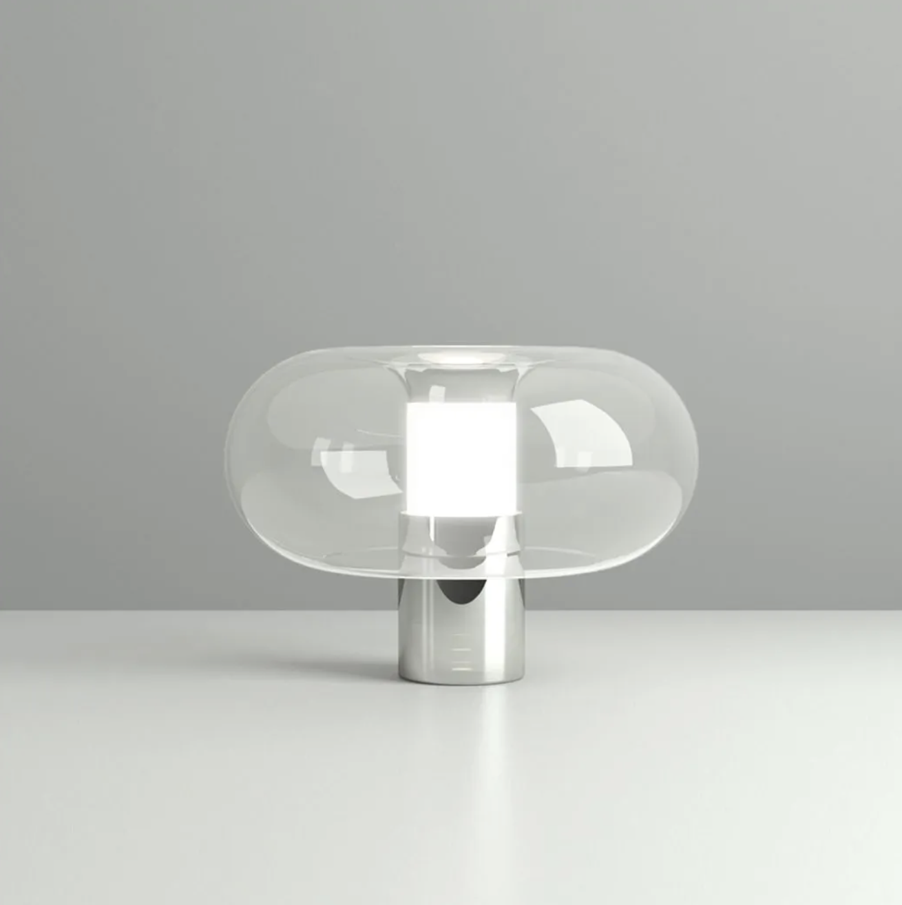 Fontanella Table Lamp - Two materials: metal and glass, as in the historic tradition of FontanaArte. The metal acts as a base and contains the light source while the glass, the true protagonist of the project, is expertly worked by skilled craftsmen in a process of fusion between a portion of transparent glass and a satin one from which the light diffuses. Fontanella is formed by the union of two glasses: the internal tube is threaded, sandblasted and finally joined with the bubble-shaped blown glass. What makes the processing particularly refined is the manual joining of the two parts, which requires the skillful technique of a craftsman. Furthermore, the glass, which has always been the material par excellence of the FontanaArte product, is the most crystalline on the market. The use of light bulbs, dimmable and not dimmable, for the biggest energy saving, complete the contemporaneity of this FontanaArte piece.