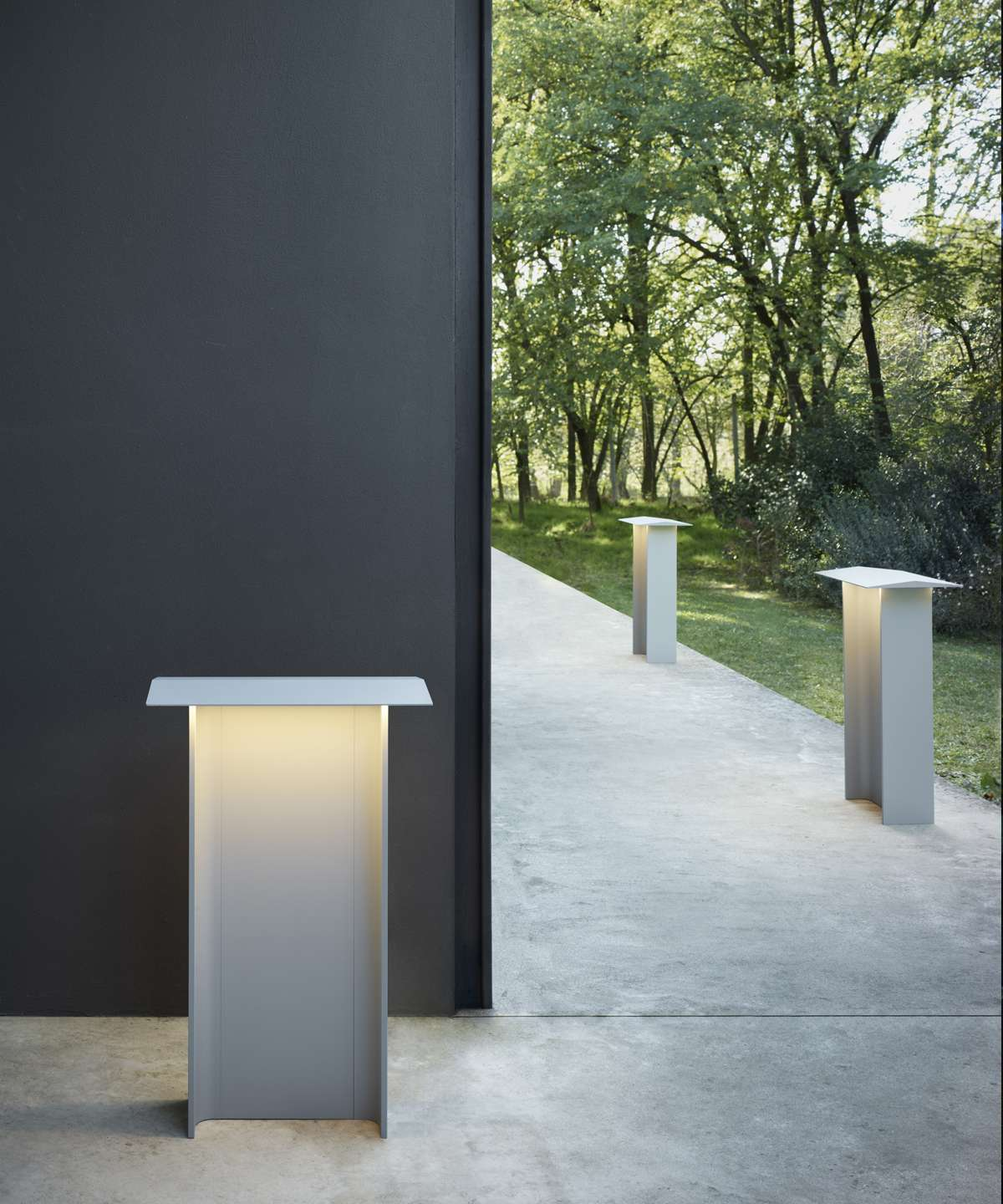 Fienile Outdoor Lamp - Fienile is also available in floor lamp versions for outdoor use, based on the same design inspired by the iconic rural buildings of Norway. Fienile Outdoor is a work of micro-architecture, with its walls and pitched roof extruded in a single, solid block of coated aluminium, while the diffuser is in polycarbonate. The outdoor version of Fienile comes in two heights, 32 or 72 cm, and two colors: pale and dark gray. Thanks to its essential design, Fienile Outdoor fits perfectly into the surrounding landscape and architectural context. The characteristic angled roof, besides being a clear reference to the archetypal form of the house, contributes to screen the light and spread it uniformly on the ground.  Come in different finishes please enquire for more information | Matter of Stuff