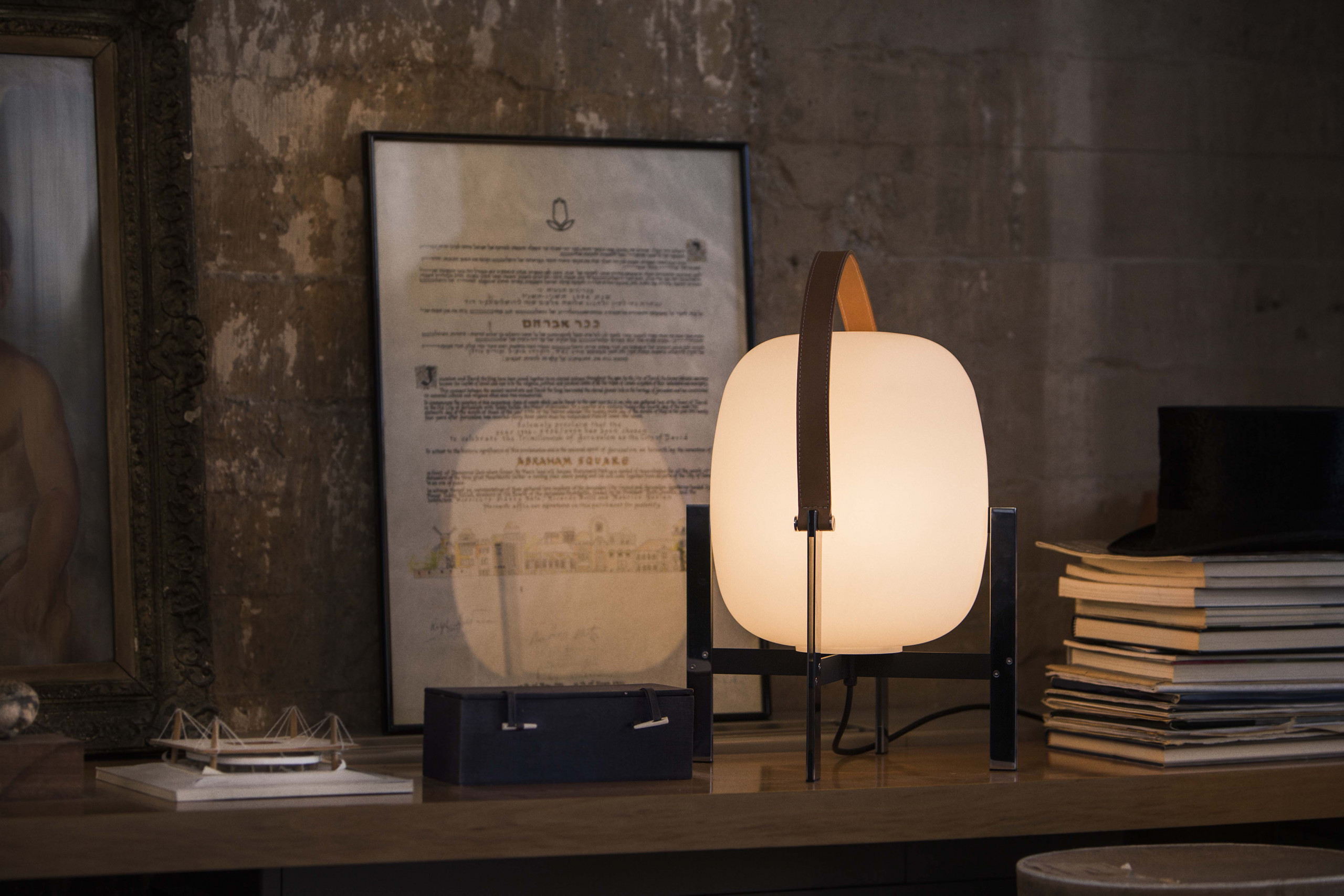 Cesta Metálica Table Lamp - <p>A duel between fragility and strength: the Cesta Metálica is the updated version of the Cesta, with its own distinct features. It comes with or without a smooth leather handle; a stark contrast to the stern, rigid structure, that gently holds an opal globe without neck. Miguel Milá mastered the strength of steel by placing at its centre a delicate opal silhouette, and a touch of soft leather. A seamless expression of strength and emotion, combined with everyday practicality.</p>    Matter of Stuff