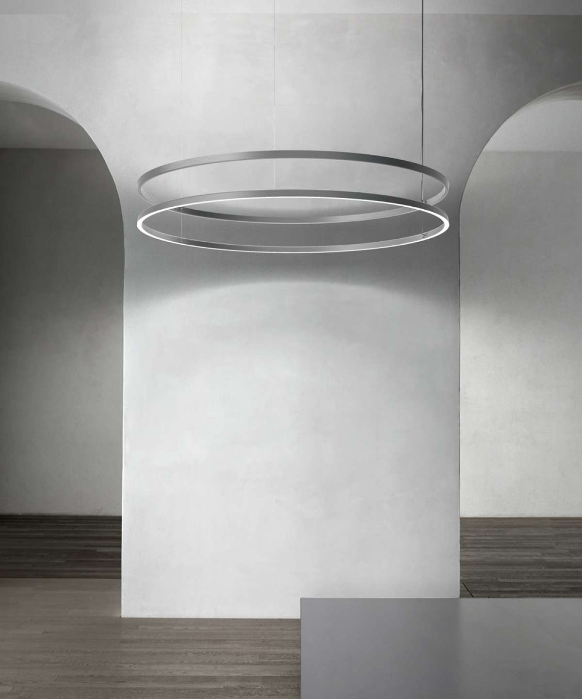 Compendium Circle Suspension Lamp - The design language of Daniel Rybakken returns to its reliance on the intrinsic power of basic geometric forms, turning this time to the symbol of harmony par excellence: the circle. An extension of the Compendium family, Circle is a lamp with a poetic nature and an essential design, whose lightness is sustained by LED technology, installed to permit direct emission when pointed downward, or diffused light when aimed upward. It is also possible to combine up to three rings of different diameters to give rise to different configurations and luminous scenarios of great visual impact.  Dimension and shape varies please enquire for more information | Matter of Stuff