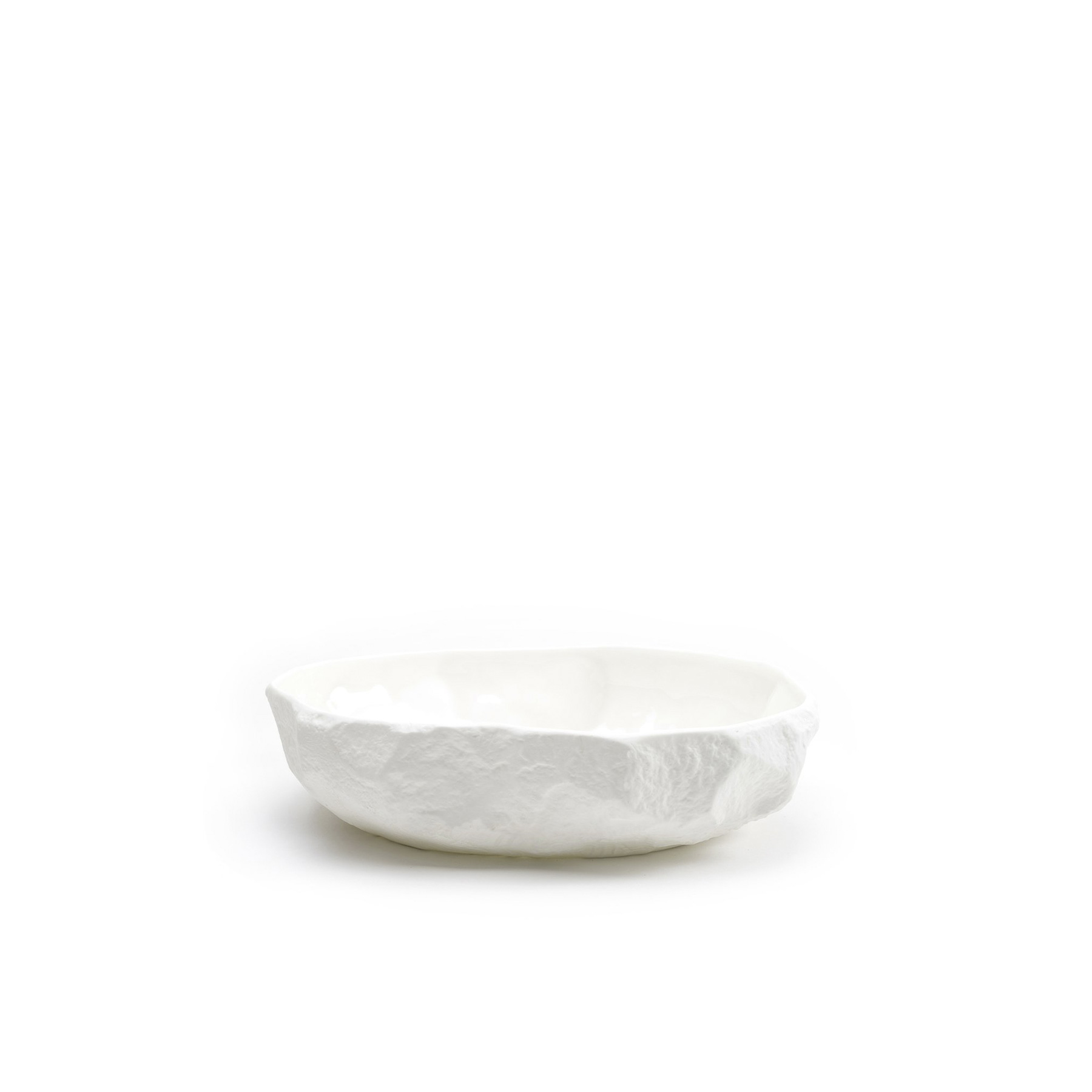 Crockery White Large Flat Bowl - A collection of fine bone china tableware slip-cast from plaster models carved by hand, with glazed interior for functionality and raw exterior reflecting the modest surface texture of the plaster original. The process of slip-casting begins with the creation of a three-dimensional model of the design known as a master by a professional model-maker, from which the production mould is cast. Crockery bypasses this process by placing the responsibility of both designer and model-maker in the hands of Max Lamb. Using the tools of a stone mason Max chips and carves a solid block of plaster to make a series of tableware, the design of each formed quite simply out of their own making. Microwave and dishwasher safe.  | Matter of Stuff