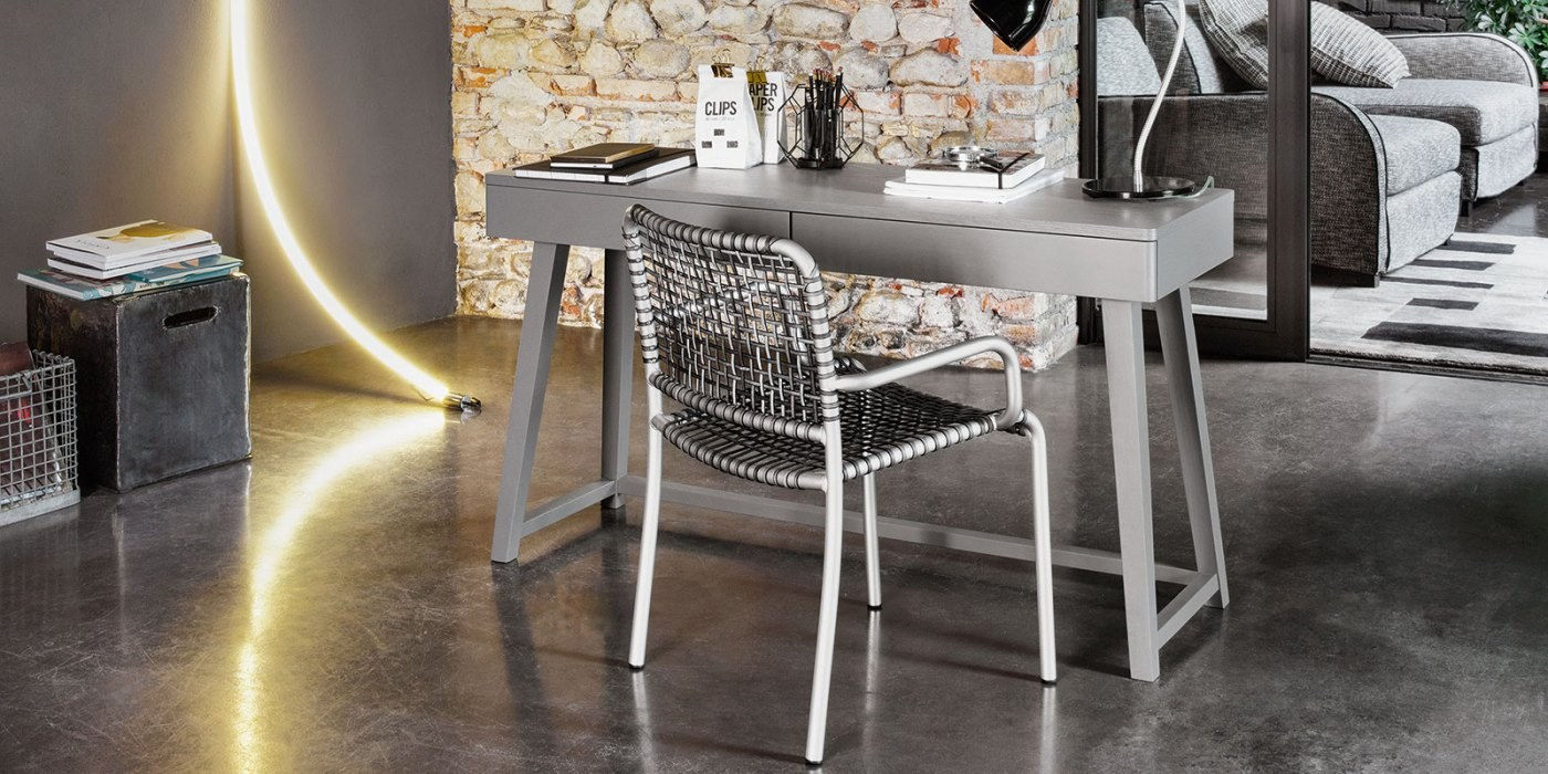 Gray 50 Desk - The Gray collection is a combination of apparently incompatible elements achieving a result which is contemporary, poetic and attractive. Gray takes inspiration from two styles, the neo-classic gustavian and the scandinavian one from the seventies. Armchairs, sofas, tables, beds and storages are the elements of this line made of a material such as turned and shaped wood, woven fibre, slate, china, marble and mirror. The plain elegance of the XVIII century furniture melts with the sobriety of the scandinavian design, which is more familiar to us. The wooden surfaces are mat and chalky, lead grey and white. grey and white are also the colours f the striped fabrics covering the models and the knit made jacquard patterns used for the cushions. Crochet laces are the decoration of the mirror front doors of the storages. China and natural american walnut are the materials which give harmony to the complete line.