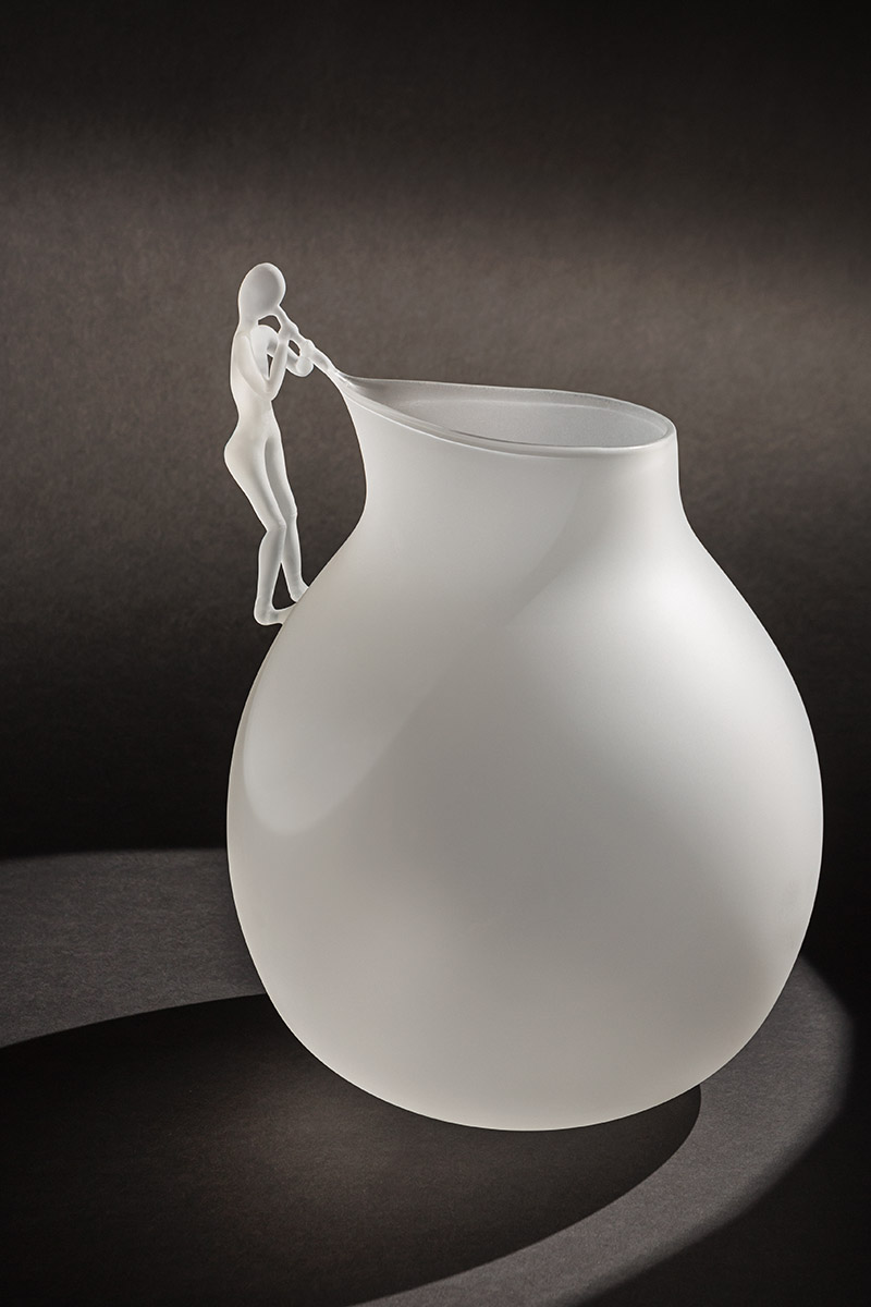 "The Blowing Man Pitcher - <p>The Blowing Man is a collection of 5 pieces in hand blown borosilicate glass in limited edition of 29 pieces, the story through the poetic and oneiric interpretation of the art of glass blowing.The collection becomes the theatre where ""man"" is once again the protagonist together with the object, and through the object itself, in a game of light and shadows that highlight the high-end handwork through the poetry of gestures delicate like breaths.</p>  
