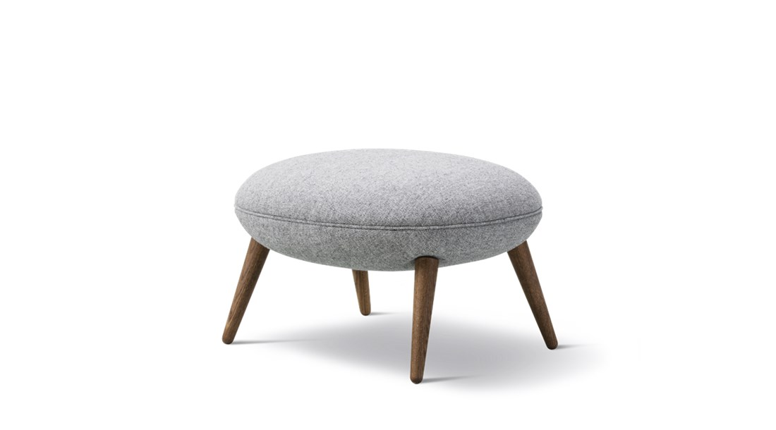 Swoon Ottoman Stool - Fredericia now presents a fully-upholstered ottoman to supplement the Swoon chair; creating a sophisticated lounge set that invites hours of comfort. With its continuous curves, lush look and sculptured shape, Swoon echoes Space Copenhagen's desire for you to enjoy life at a slow pace.   Originally launched for the 11 Howard Hotel in New York, the Swoon Lounge is an open invitation to luxuriate in comfort. Based on their extensive experience designing high-end hotel interiors and Michelin-star restaurants, Space Copenhagen created Swoon to fill a gap missing in the market – a hybrid of a lounge chair and an armchair with the benefits of both. The singular shell merges the back, seat and armrests into one entity, allowing for exceptional support and a fit that feels natural. The seat and back cushions are also attached as one piece for endless hours of comfort.   Swoon is suitable for hotel lobbies, VIP suites, restaurant reception areas, upscale bars, lounges and private residences.   Of course, the perfect companion to any lounge chair is an ottoman. The Swoon Ottoman not only adds to your ability to stretch out and relax even more, it's a decorative element in its own right. Ideal as a pouf for punctuating any space with style.   Look for the same casual take on elegance in the Swoon Lounge Petit. Slightly smaller in size, it features a high back designed at a more upright angle. The result is a chair that invites you to unwind, making it conducive for conversations or working on your laptop. | Matter of Stuff