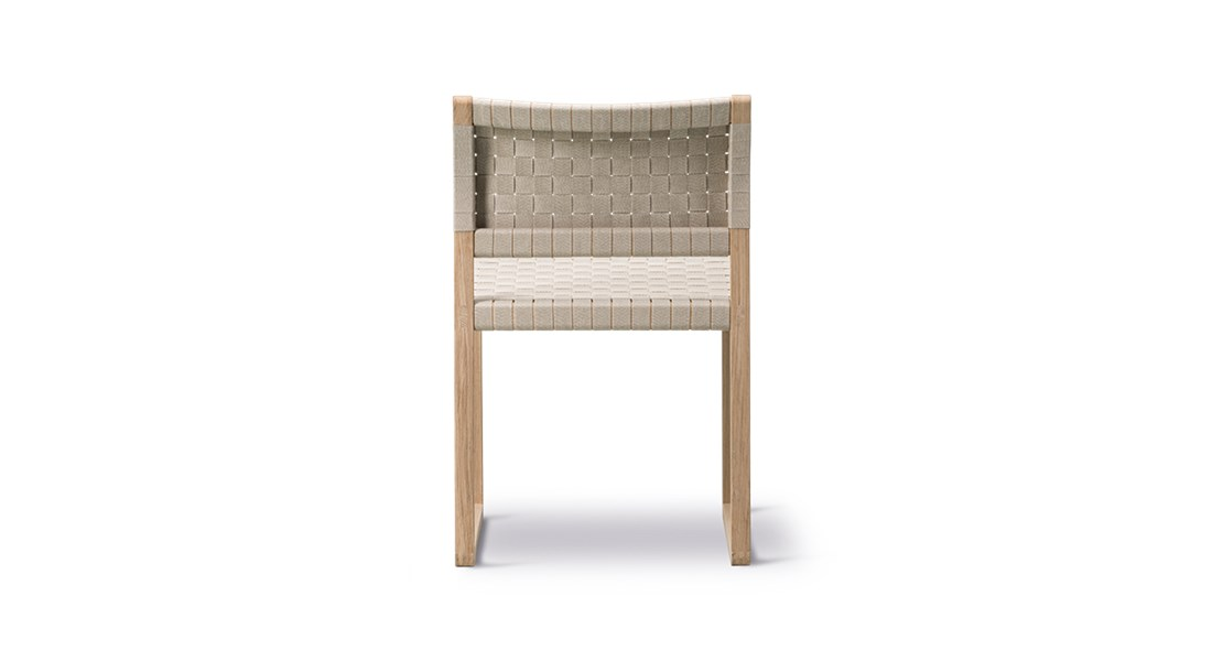 BM61 Chair Linen Webbing - Børge Mogensen brings us back to nature with the choice of cane wicker or linen webbing coupled with a solid wood frame. In a slender design involving only what's crucial to the construction. By carefully calibrating the angle of the back rest, it's a simple yet striking dining chair that's comfortable before, during and after dinner.  Two versions in two different natural materials attest to Børge Mogensen's talent for pared-down shapes elegantly engineered for comfort. Dispensing with anything extraneous in favour of clean lines in a pure, iconic design that defies any temporary trend.   Both the BM61 Chair and the BM62 Armchair exude a certain authenticity. Designed with an exposed construction that reveals immaculate joinery and hand craftsmanship. Along with the choice of honest materials, such as natural cane wicker or linen webbing in natural or black for the seat and back together with a solid wood frame. It all reflects our expertise in materiality since our inception.   One glance at the chair in profile and you'll notice a slight angle to the rear post, which changes to provide optimal support for the back. With the lower section supporting the small of the back in an upright position, and the upper part providing support in a more relaxed position. What's more, the sledges not only ensure continuity, they're the perfect choice for soft floors.   As a dining chair, the BM61 Chair and BM62 Armchair are a comfortable seating solution for before, during and after dinner. Ideal for top-star restaurants, hotels and private homes. Choose the side chair or armchair, and you have a statement piece that is suited for galleries, museums and cultural centres. Luxury retail and residential settings, executive environments and more.  | Matter of Stuff