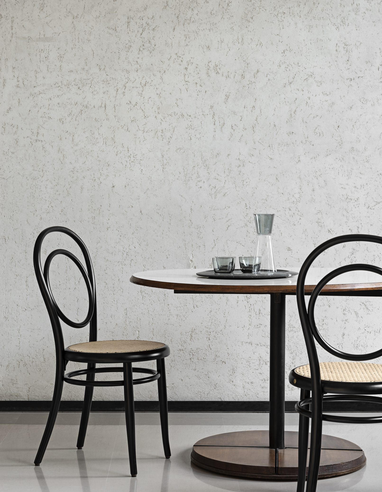 N.14 Black Chair - This exceptional chair reinterprets the elegance and timeless charm of the classic bistro chair. Every element that composes its structure is crafted of solid beechwood bent using steam, creating the elegant curves of the back and the rings below the plywood seat. Entirely veneered in black, this piece will be a superb addition to a modern dining room. It is also available with seat in Viennese cane or perforated plywood, please ask the Concierge for details.    Matter of Stuff
