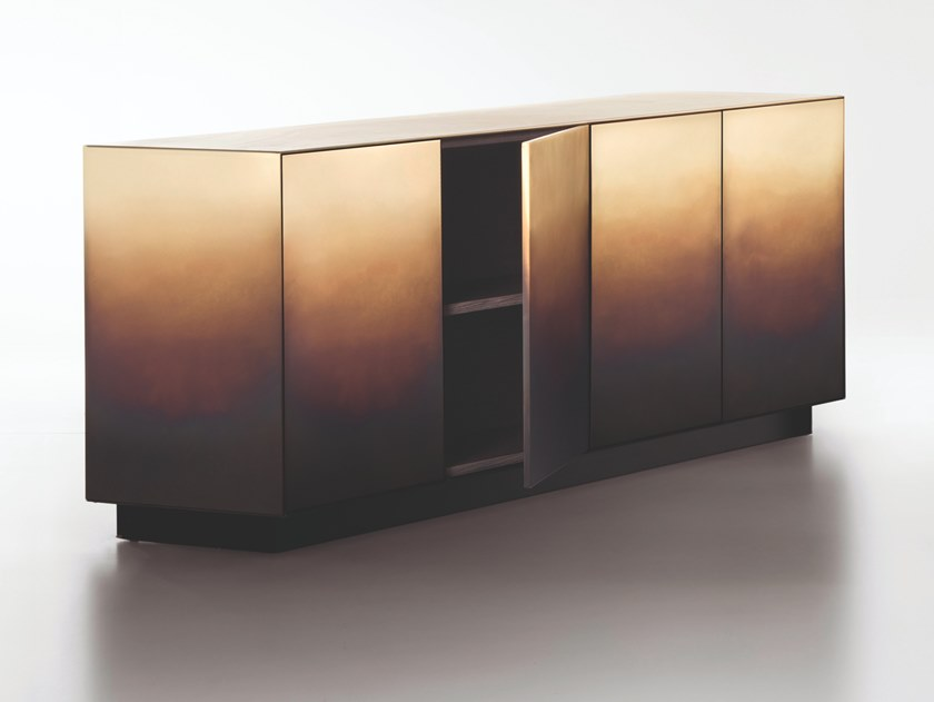 Marea Sideboard - The traces of time are drawn one on top of another, infused into the changing skin of the rigorous metal forms that define these cabinets and chests. Like the tide (marea in Italian) leaves its mark, wave after wave, even here the hand of the craftsman has left its sign, oxidation after oxidation, creating a painterly effect that resembles water's erosion of the material. Somewhere between design object and work of art, each piece in the collection, composed of a chest of drawers, low credenza and cabinet, is unique thanks to an entirely hand-crafted finish that transforms the metal surface into a delicate watercolour.  Collection of 3 containers clad in metalon all sides. Doors and drawers withpush-open system and full extensionMovento Tip-on Blum slides.  The sideboard comes in 3 different sizes and materials: Iron, Brass and Copper. Inner Structure is in titanium oak | Matter of Stuff