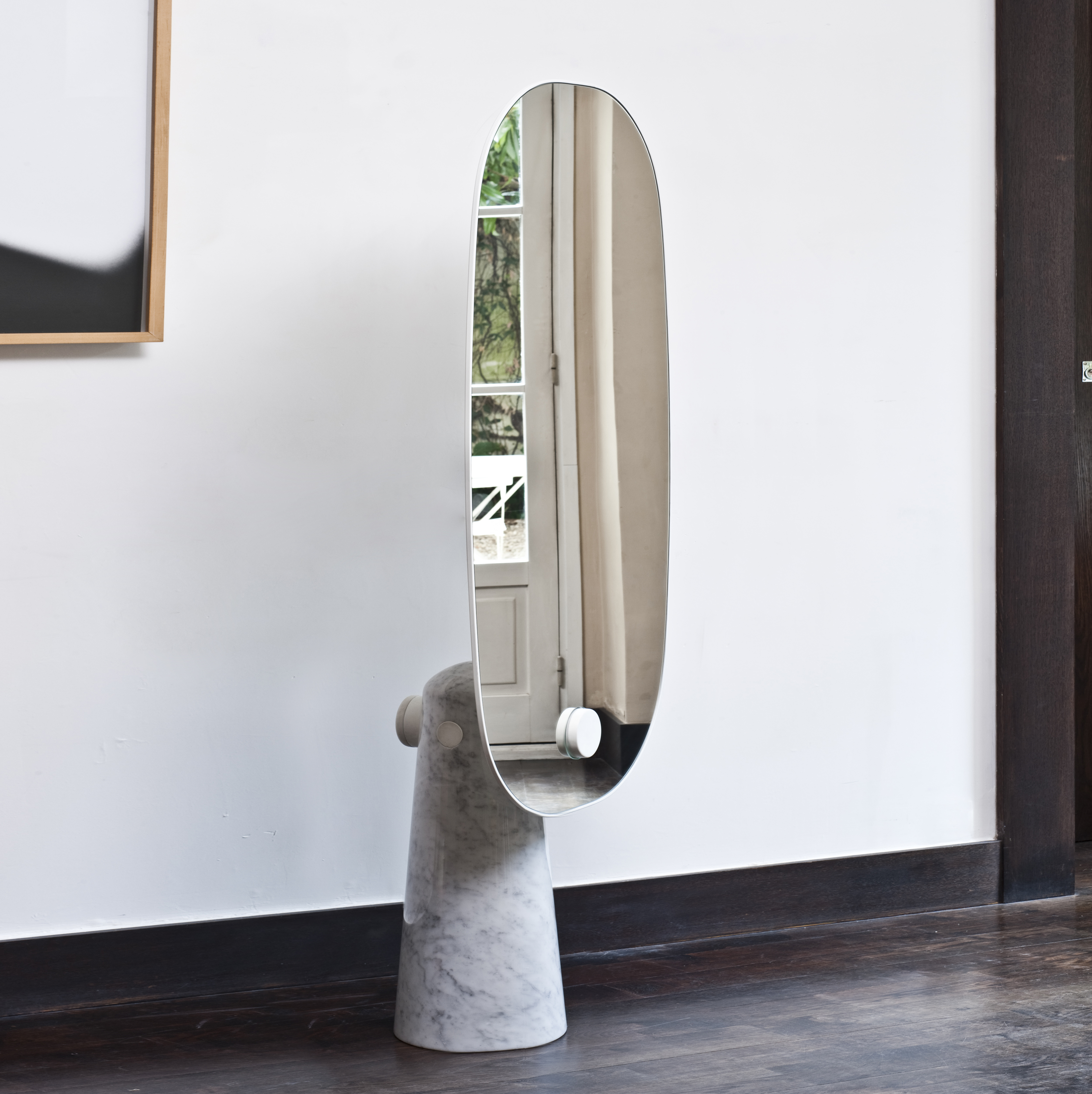 Iconic Standing Mirror - <p>Iconic is a mirror that stands as a statue. The marble – or wood - pedestal contrasts with the thickness of the mirror it supports. The metal cylinder sealed to the base makes the structure literally cross the mirror.</p>