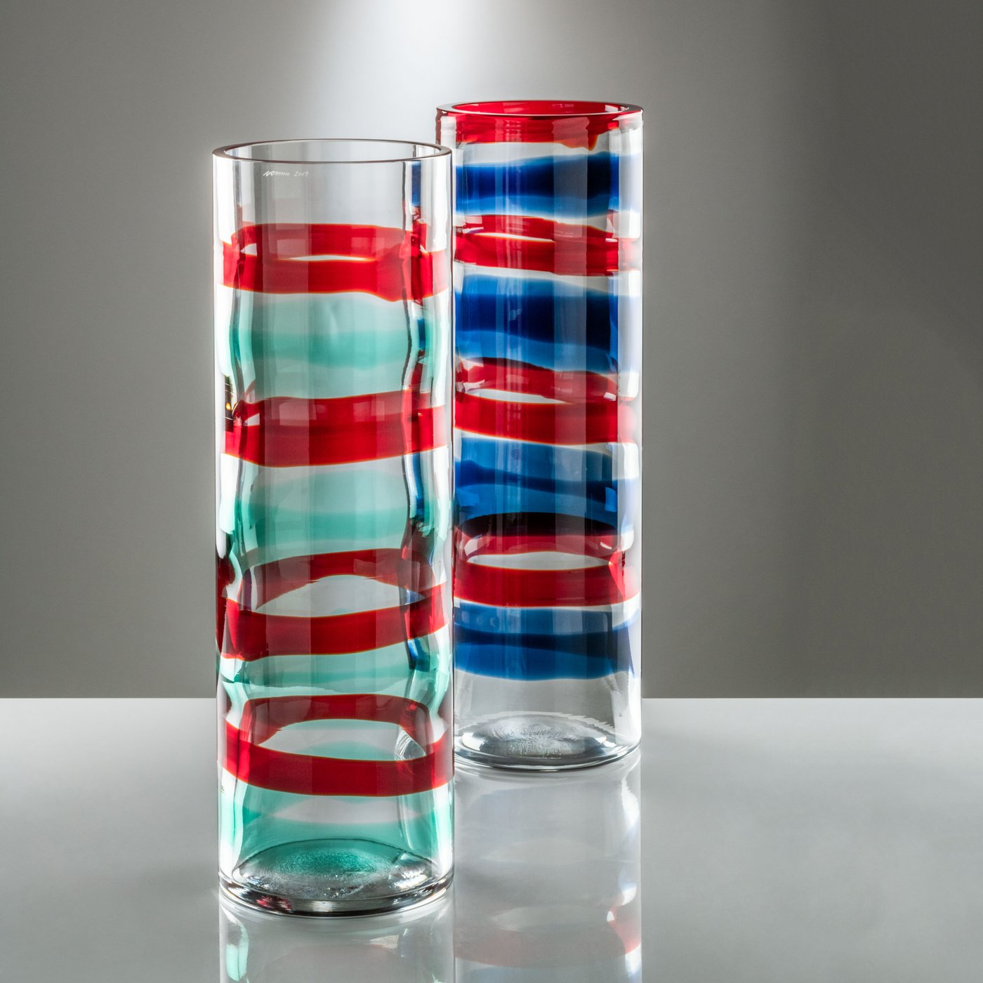 """Anelli Vase - As part of Venini's 2019 Amazing Colours collection, the Anelli vase is a piece of great importance, both in size and in the chromatic aspect. On the transparent glass, alternating rings of colour are applied before blowing, creating a unique vessel that is both playful and sophisticated. Handmade by master glassmakers on the island of Murano, Italy. Please note: dimensions and colours may vary due to the handcrafted nature of this product.  """"The master skilfully plays with sheer glass: four red rings alternating with four light blue or blue ones, running its full length. A new glass star is born in 2019: Anelli. Color is hot-applied before blowing the glass, thanks to the exclusive Fasce (bands) technique."""" 