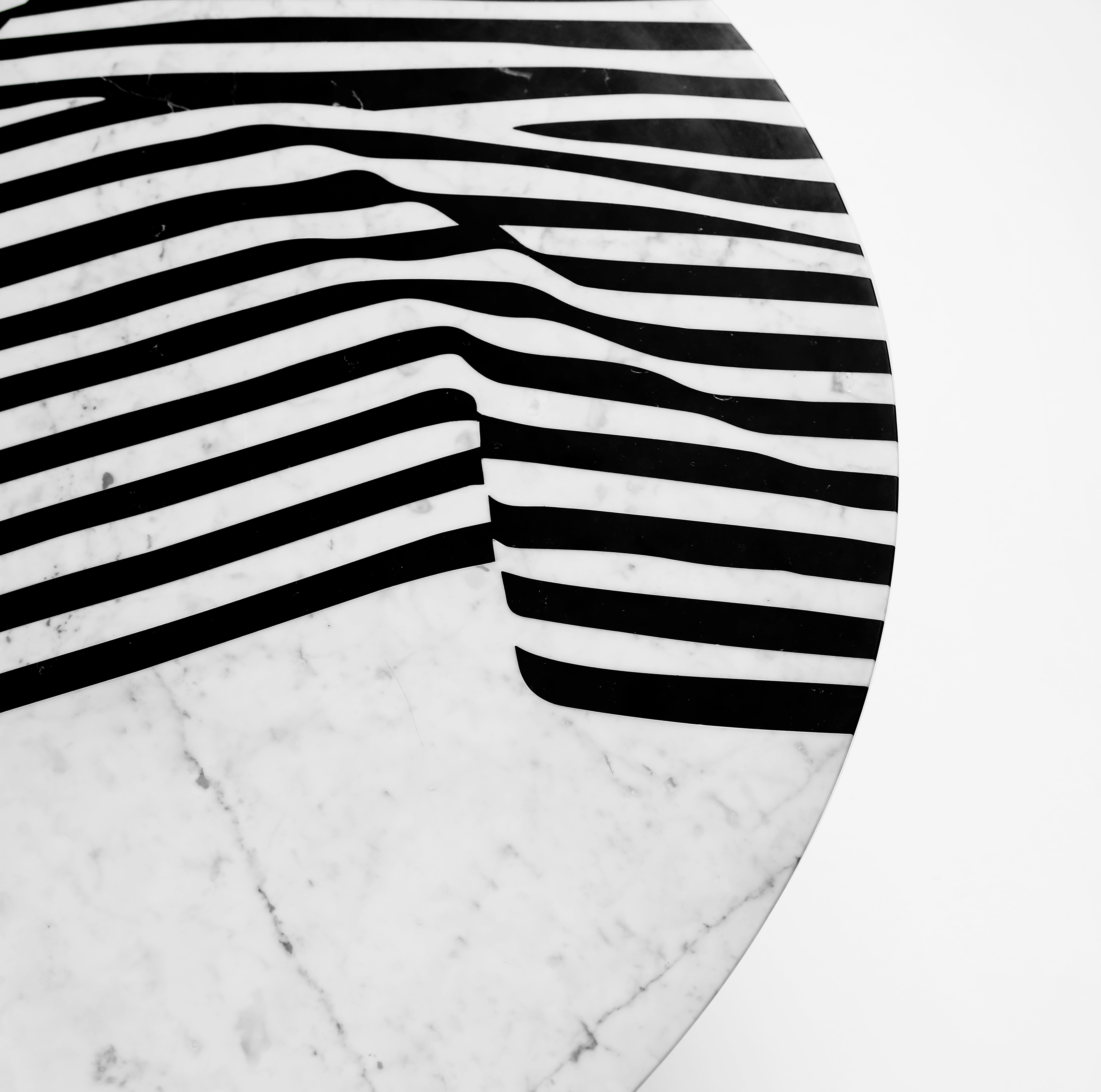 """The Veiled Dining Table - <p>The Veiled is a collection of tables and trays made of marble with a graphical pattern inspired by an ancient statue.<br /> It experiments with the dichotomy between a silk and soft looking surface for a hard material like marble.<br /> The effect of light and dark-coloured marble in stripes is both graphic and illusional.<br /> The pattern catches your eye and invites you to touch.<br /> It combines a modern technique and aesthetic with the traditional way of making inlays.<br /> Developed and Produced during the """"Matter of Stuff Designer Residency"""" program in Montalcino, Italy. </p>  Dining table in marble available in two versions: with three marble legs or one metal base.  