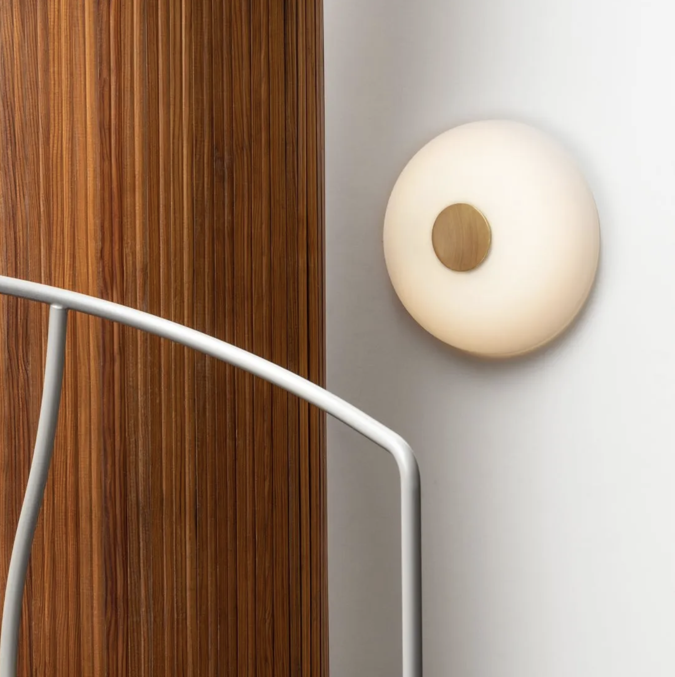 """Tropico Wall Lamp - The """"shape of light"""" is the central theme of this project by Gabriele and Oscar Buratti, which began with the Equatore family of lamps, presented in 2017 and now expanded to include other finishes, and continues with the new Meridiano and Tropico. Forms of glass and metal that collect, contain and diffuse light in space. Passing between opaline, coloured and transparent layers, emphasised by the refined curves and the magic of blown glass, the light is free to create surprising and fascinating effects, patterns and moods. Tropico is a spherical cap of opaque opaline glass, flattened and fixed by a large mirrored metal boss. The family comprises wall/ceiling and table versions, both available in three different sizes.  Wall lamp with diffused phase-cut dimmable light. Diffuser in etched opaline blown glass. Central button available in gold or black nickel-plated. Integrated LED.  