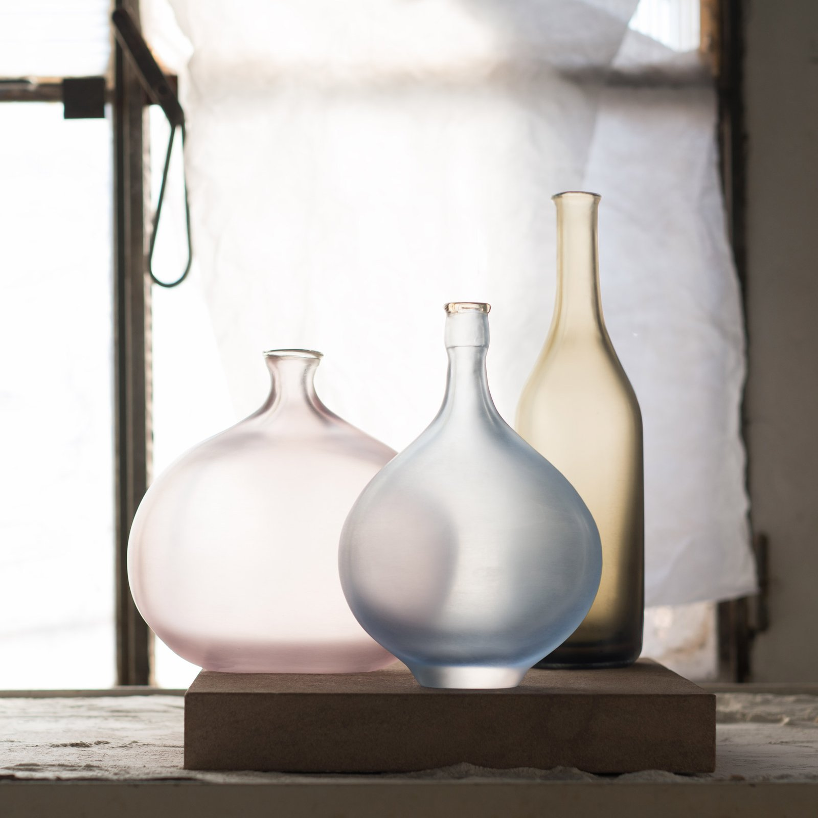 """IL Silenzio Dei Colori - Designed by Matteo Thun for Murano glassmakers Venini, the Il Silenzio dei Colori collection consists of four different sets of glass objects inspired by Italian painter Giorgio Morandi. Produced from blown-glass and expertly finished using cold-processing techniques, the vases and bottles feature a smooth translucent finish. Finally, each limited-edition set is presented on a Santafiore stone tile. This particular set comprises of three vessels in Violet, Marine Blue and Grey. Please note: dimensions and colours may vary due to the handcrafted nature of this product.  """"Now it's the colours that are left speechless, their silent words are so profound that only the eye can perceive. This is the magic that makes each and every one of the four combinations created by Matteo Thun in 2018 truly unique."""" 