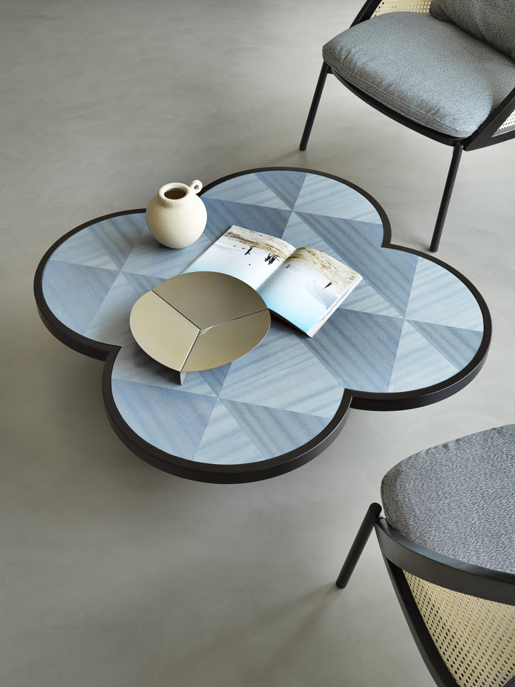 Caryllon Low Table - This coffee table boasts a wooden structure with a modern square section, a striking contrast with the round and sinuous lines of the base and top. The standout feature of this stunning piece is its top, adorned with a sophisticated, handcrafted inlay method that uses strips of straw to create a motif inspired by the Viennese straw. The rich blue color is inspired by the opulent Art Deco style.