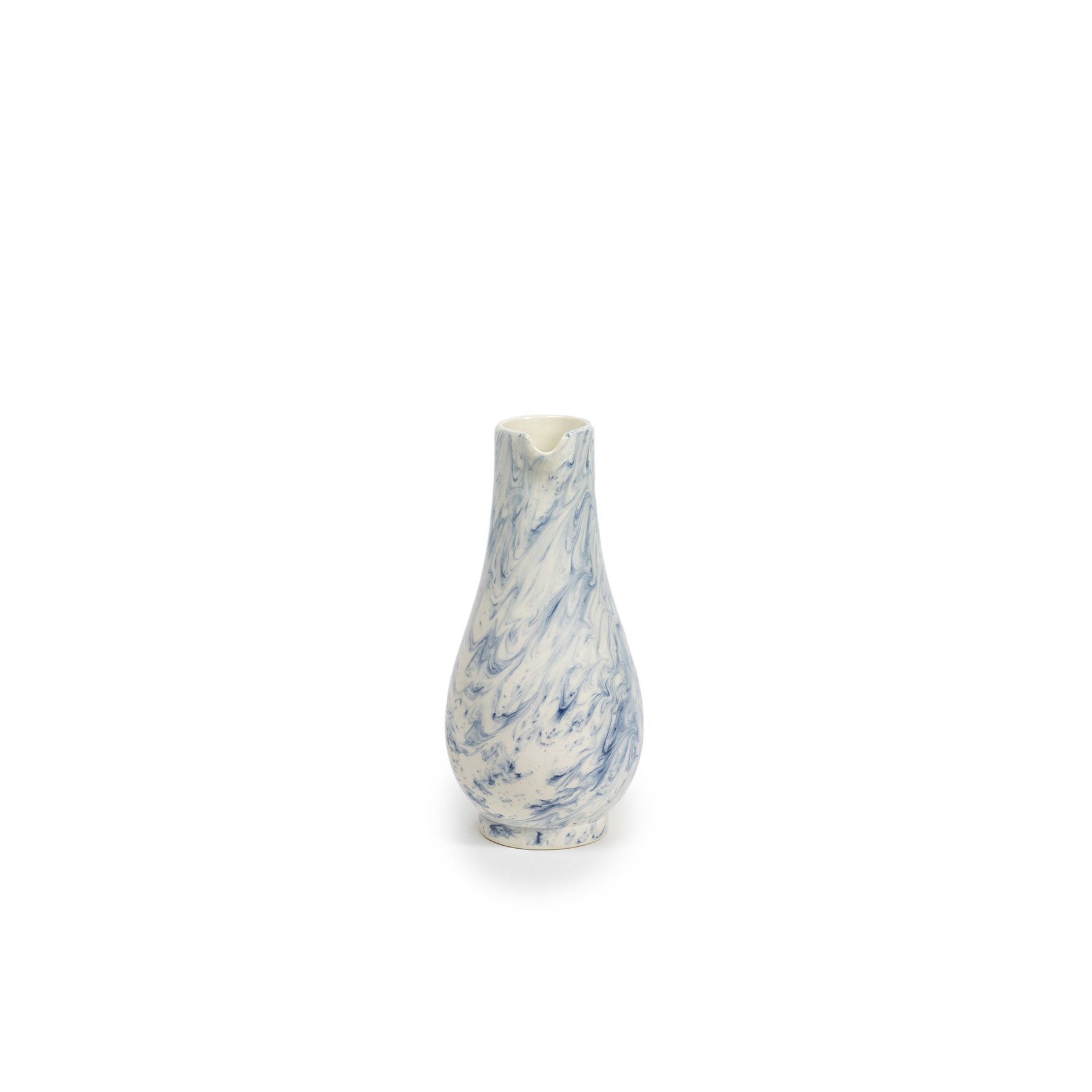 Indigo Storm Jug - Faye Toogood's range of ceramic designs for 1882 Ltd. celebrates the serendipitous beauty of natural imperfections. Indigo Storm, a new interpretation of traditional creamware forms, draws upon the chance patterns created when pigment added to the slip coating does not fully blend. The whorls and eddies resulting from these experiments, like meteorological formations in miniature, make up the collection's central motifs, appearing on pieces including plates, bowls and cups. Representing a streamlined take on our ceramic heritage, the fine earthenware employs the familiar tones of English Delftware: cream offset with a rich, deep blue. Dishwasher and Microwave safe.  | Matter of Stuff
