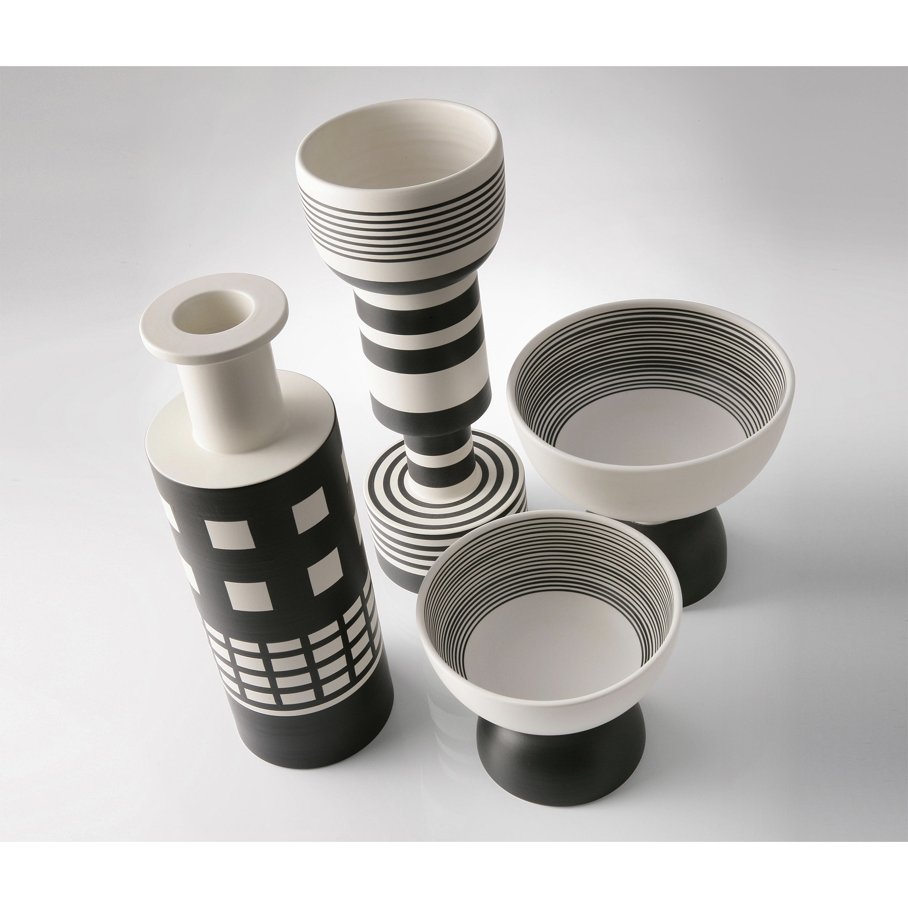 Goblet Tall Vase - Goblet vase B&W series. Hand-turned in white clay. Two-tone matt black and white glaze. This elegant vase was designed by famous Italian architect Ettore Sottsass in 1962. It is in white clay and its geometric shape with a white finish is adorned with a series of parallel black lines of different thickness, for a striking final result. | Matter of Stuff