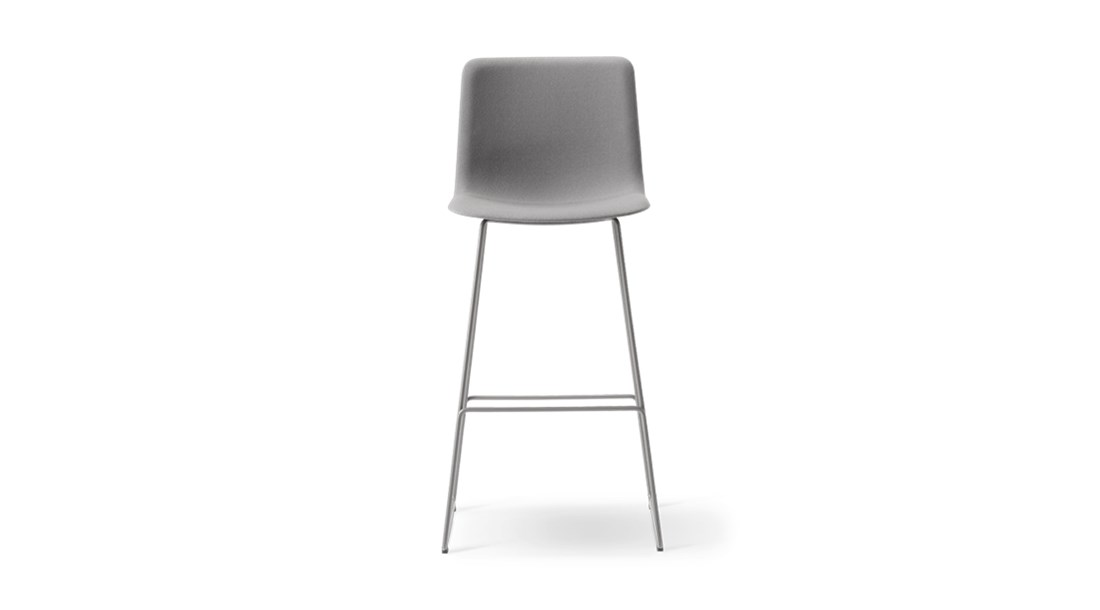 Pato Sledge Barstool Fully Upholstered - Pato is a carefully crafted multipurpose chair in eco-friendly polypropylene that can be used outdoors. The chair is available with a range of optional features including coupling. The chair can be tuned from basic to exclusive with optional upholstery.  Pato is a prime example of our focus on sustainability and protecting the environment, reflected in a chair that's 100% renewable and recyclable. All components can be incorporated into future furniture production, thus contributing to a circular economy by minimising the use of materials, resources, waste and pollution.   Merging traditional production methods with cutting-edge technology, Pato is a human-centric, highly versatile series of multi-purpose functional furniture that draws on our in-depth experience with materials, immaculate detailing and heritage of fine craftsmanship. Allowing us to apply our high standards of texture, finish and carpentry techniques to an array of materials in addition to wood for products aimed at a mass market.   With its clean lines and curves, Pato echoes the ethos of Danish-Icelandic design duo Welling/Ludvik. Demonstrating their belief that good design has the ability to be interesting, even when reduced to its most simple form. Where anything extraneous is eliminated and every detail has a purpose.   Together we spent nearly three years developing the shell structure to have a soft surface that's also wear and tear resistant. Enhancing the chair's ability to optimally conform to the user's body is a subtle beveled edge. A technique from classic cabinetmaking, which gives the chair a sense of handcrafted finesse. Each Pato is detailed and finished by hand by our highly skilled crafts people, who refine the beveled edge and the silky, resilient surface. Setting a new standard for the execution and finish of polypropylene.   Since the success of its initial launch, we've expanded Pato into an extensive collection of variants, featuring a