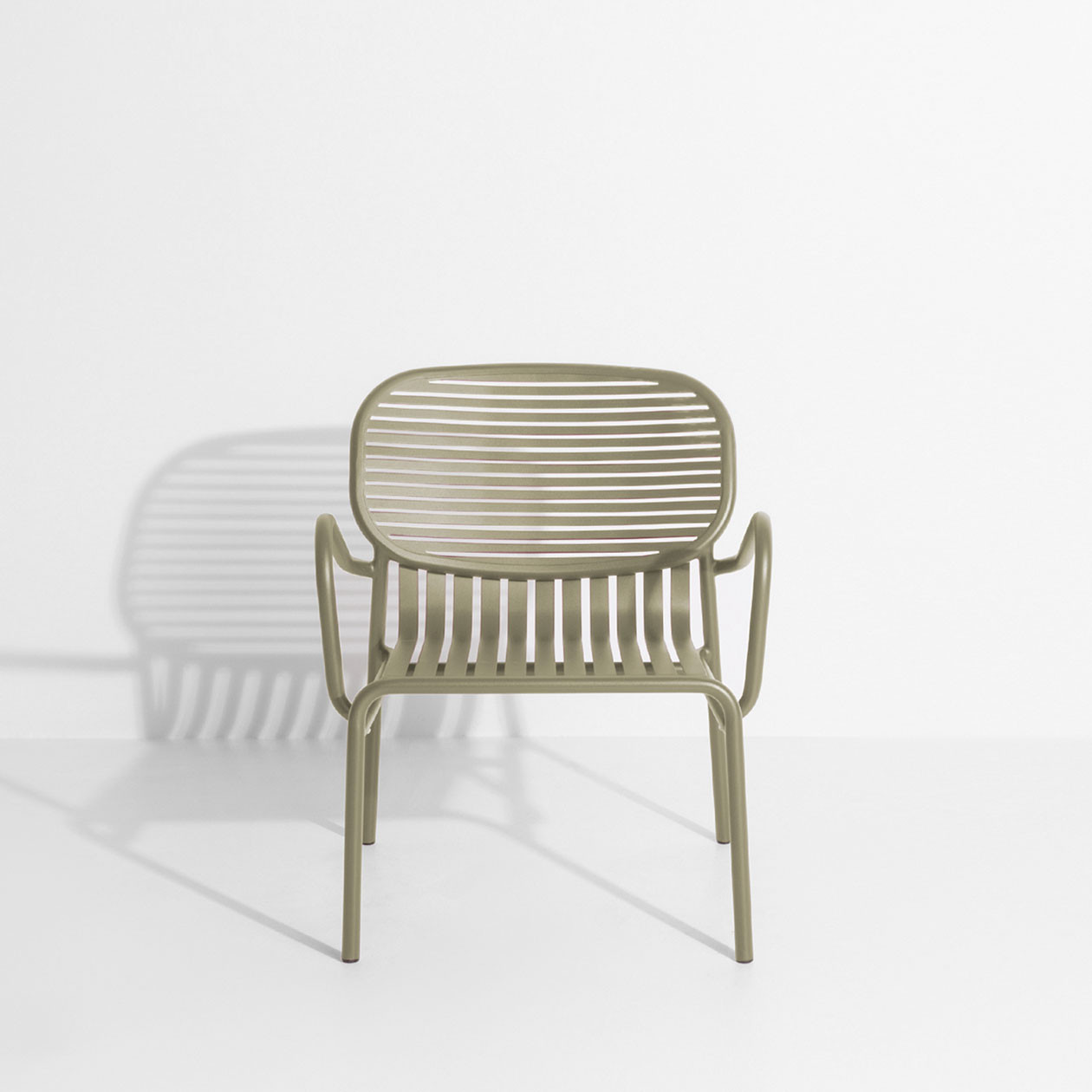 Week-End Armchair - The WEEK-END collection is a full range of outdoor furniture. Designed with practicality in mind, all of the seats are stackable. The Week-End collection is a complete range of outdoor furniture. The oval and circular shape drawn by the backrests makes them a graphic statement. The impact of the horizontal and vertical slats, so similar to stripes, highlights the full and empty spaces, asserting the identity of the collection.