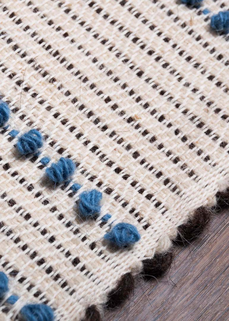 "Pibiones - Pibiones technique is realised through the use of bars to which a large wool weft is wrapped around. This passage creates a very compact curl, reminiscent of a small grape, which in the dialect of Sardinia is called ""Pibione"". The result is a very heavy fabric, 5 to 10 mm thick-depending on the size of weft and irons, characterised by a dotted texture. 