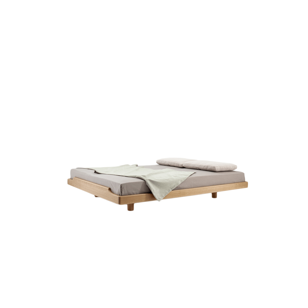 Eclair Petit Bed - ECLAIR PETIT – the bed with soft contours. The ECLAIR bed is characterised by its concise outer contours. The minimalist frame construction encompasses the mattress on top. The foot section rises with a swing – a gesture like an embrace that offers security and support. The soft, consistently surrounding edge radius condenses the quality and beauty of the solid wood. The pleasant feel creates a tangible softness. The promise of an undisturbed, carefree night.  Eclair Petit bed is available in white oiled ash, oiled oak, colour stained oak, oiled American cherry, oiled American walnut and oiled European walnut.   Available in different sizes at an additional charge upon request.  For colour stained oak, please refer to the catalogue.  | Matter of Stuff