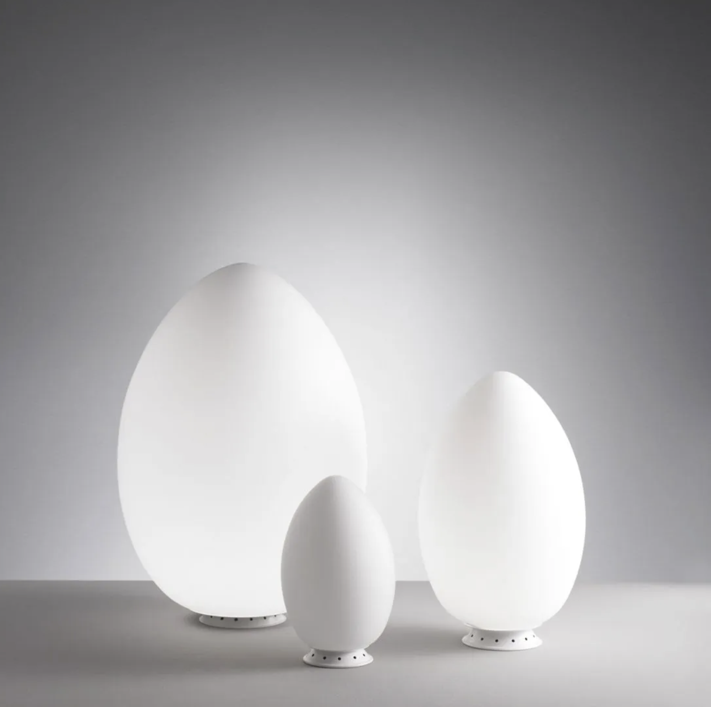 Uovo Table Lamp - A natural form and timeless symbol of perfection, in which symmetry and asymmetry harmoniously coexist. Designed in 1972, the 'shell' of the egg contained a light source: an ironic idea that still works today. As in nature, the shell of the Uovo lamp is the embodiment of absolute lightness, an elegant form in white satin blown glass that gives off a warm, uniform light. Available in three sizes, it has all the versatility of a collection designed for multiple uses: from the small version which serves as a tiny utility lamp to the large version, a veritable light sculpture, protagonist of any space.  Table lamp with diffused light not dimmable. Diffuser made of white blown glass with satin-finish. Base made of white painted metal. Black power cable, plug and switch. European two-pole plug. Bulb not included. | Matter of Stuff