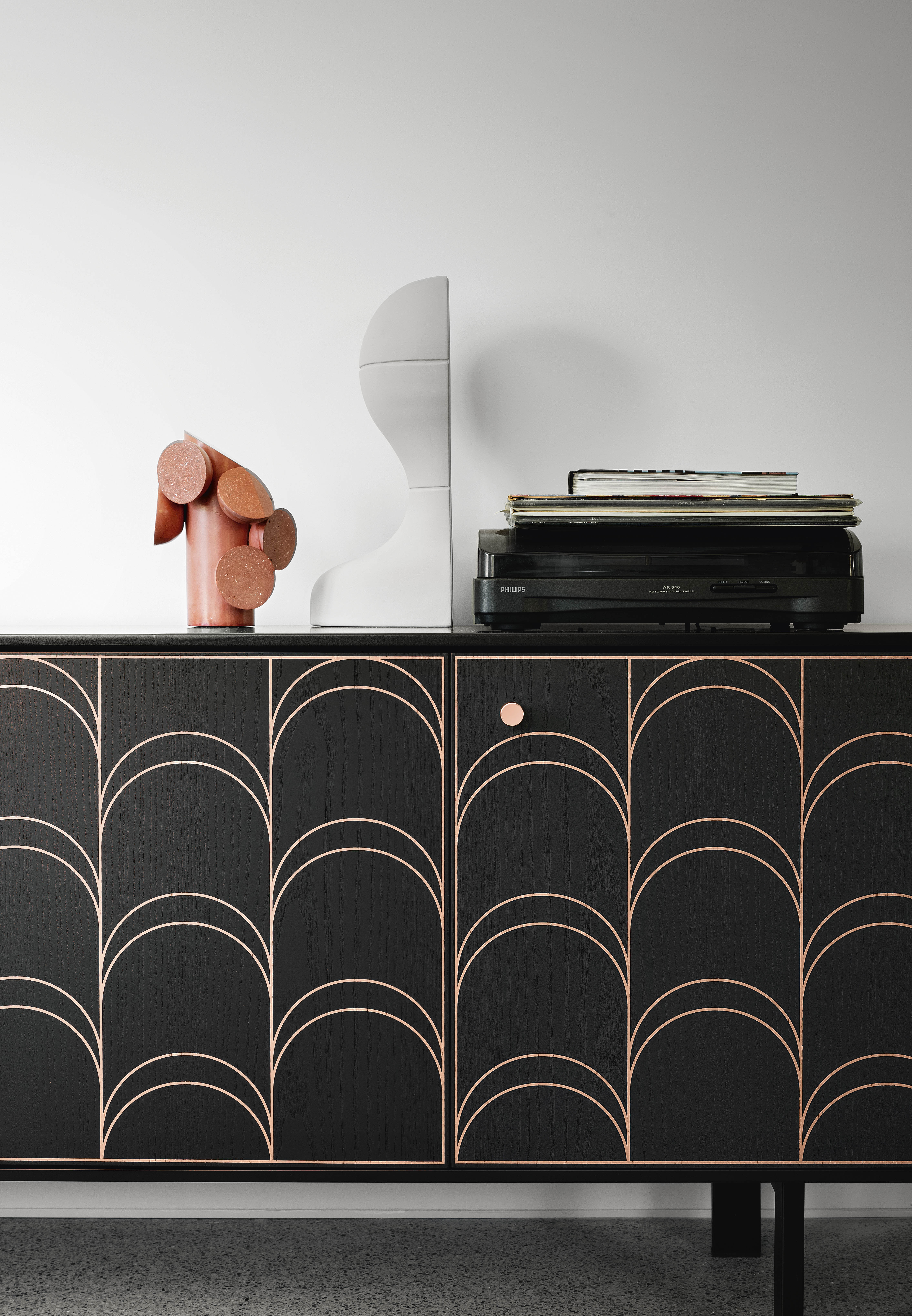Célia Sideboard - Célia takes inspiration from the Art Déco movement of the 1920s and brings it to a current, highimpact context. The protagonist is the decoration which reminds us just how much a weave can enrich an environment, conversing with different materials such as wood and copper. The doors open like a book whilst the pattern is silk-screen printed on ash or walnut. A range of materials, colours and sizes are available in a number of combinations.   An Integrated vase and air purifier are available to purchase at extra cost  Prices may vary. Please enquire for full details.  | Matter of Stuff