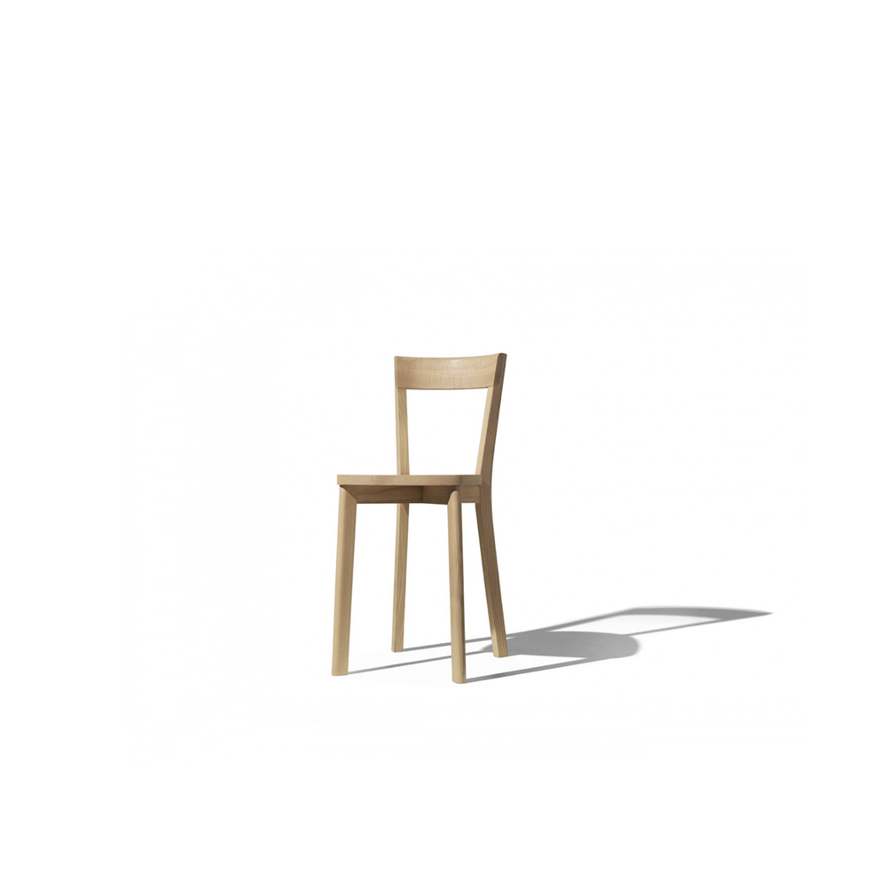 """Mina Chair - A chair made entirely in solid ash wood. Mina is a """"minimal"""" seat, reduced in its proportions – about 10-15 cm less bulk than normal chairs – without sacrificing the elegant form that suggests the style of certain seating designs by Gio Ponti. The design research has focused on keeping the right balance of form, size and comfort. Mina is one of those products that are created to be of true """"service,"""" performing at their best in tight spaces, as is often the case in French bistros, where space is exploited to the utmost to squeeze in the largest possible number of customers. Certain constructive details give the chair a unique character, including the very precise relationship between the back and the rear uprights (in which the back is completely enclosed), and the colour variations specified with extreme care by the designer.  