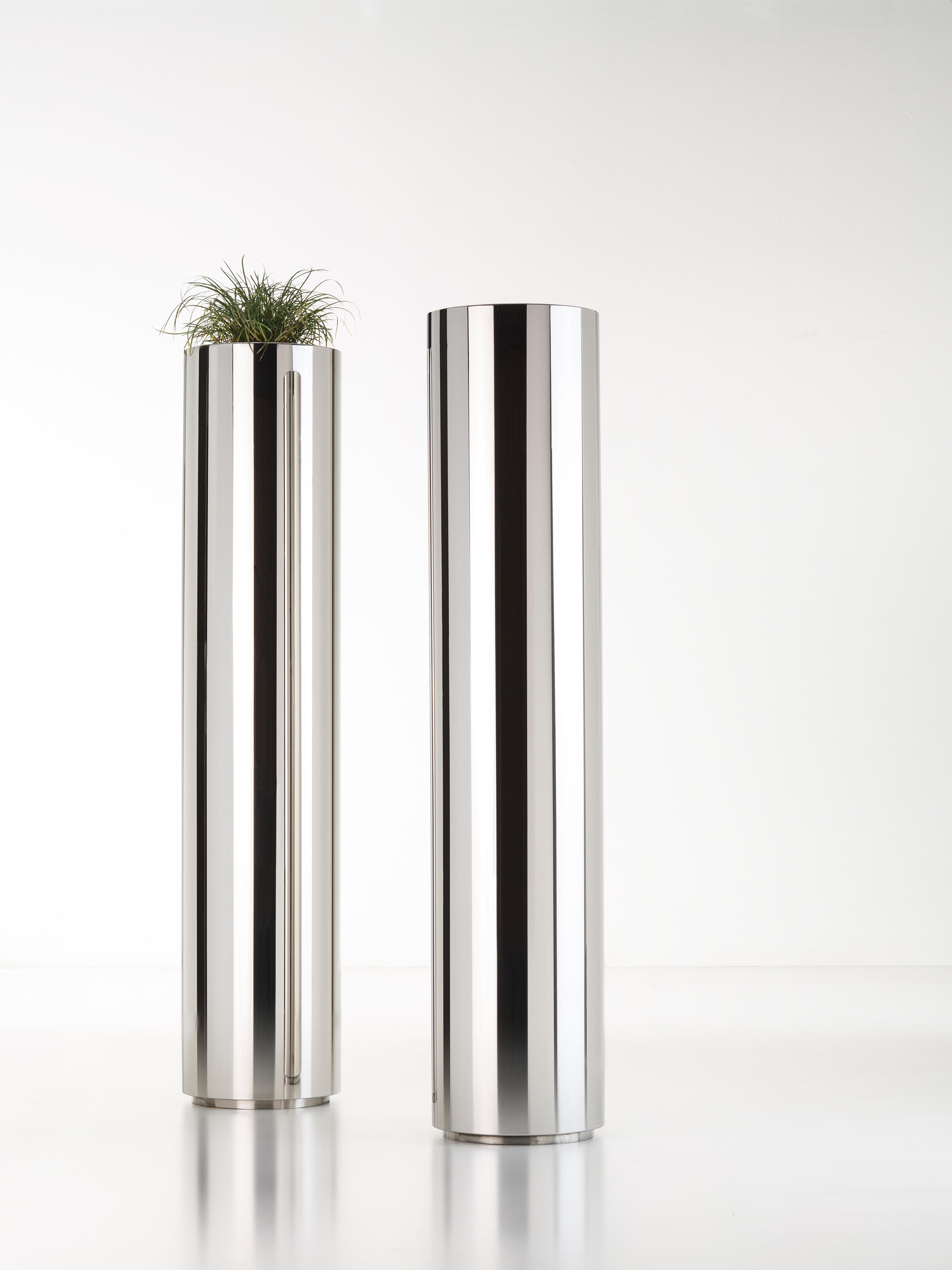 Cohiba Metal Cachepot - A pure cylindrical shape comes in De Castelli metals and finishes for a series of cachepots with abounding stage presence. In their linear simplicity, these objects become landmarks for the home, not just accessories but also cardinal points that orient the space. In different heights and diameters, they stand alone or make up multi-faceted sets.  Cylindrical metal cachepot. Closedbase for indoors or perforated base foroutdoors. Provided with an inner plasticpot to hold plants. Fixing plate availableon request. | Matter of Stuff