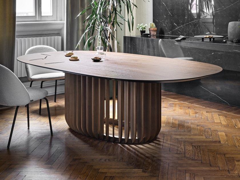 Juice Oval Dining Table - Juice is a monumental table with a meditative air.‎ Its essence lies in the base, where the long wooden legs attach to a ring, encircling it.‎ Juice, a table developed around the balance between filled and empty spaces, creates a sensation of perfect calmness.‎ | Matter of Stuff