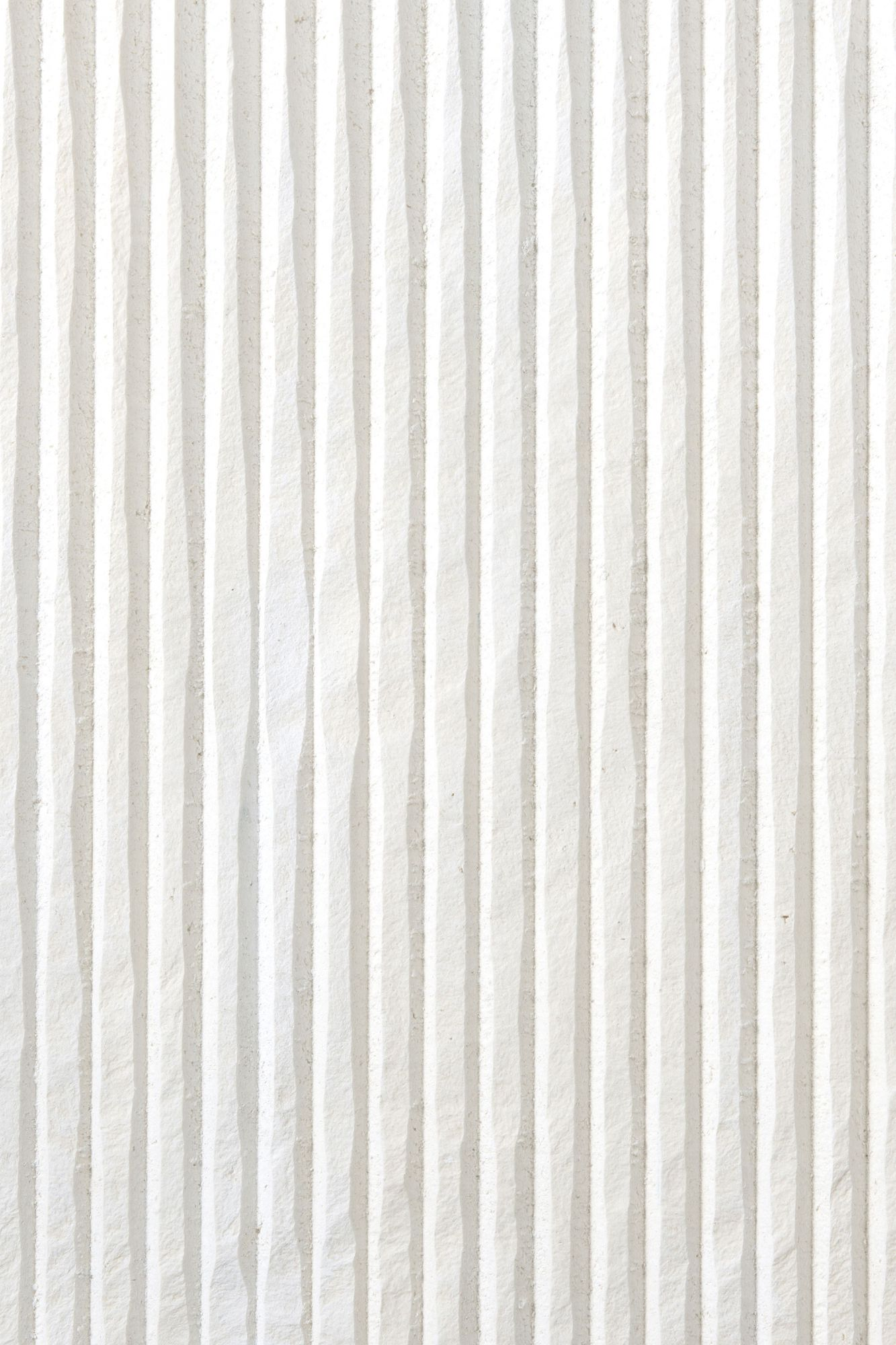 "White Big Ruts - Obtained by stretching the impasto first by hand and then with CNC machining, Ruts alternates between flat portions, reminiscent of stone, to rectangular sections to create a succession with a solid and fortunate rhythm. The ""cadence"" of its grooves can be more or less dense, continuous or interrupted, but in each of its versions and in all the different colors, Ruts reveals, thanks to the intervention of the machine, the material uniqueness of paper pulp. They are indeed hard, mechanized cuts that speak of the very fiber of the paper as it pushes toward new dynamic and formal borders. 